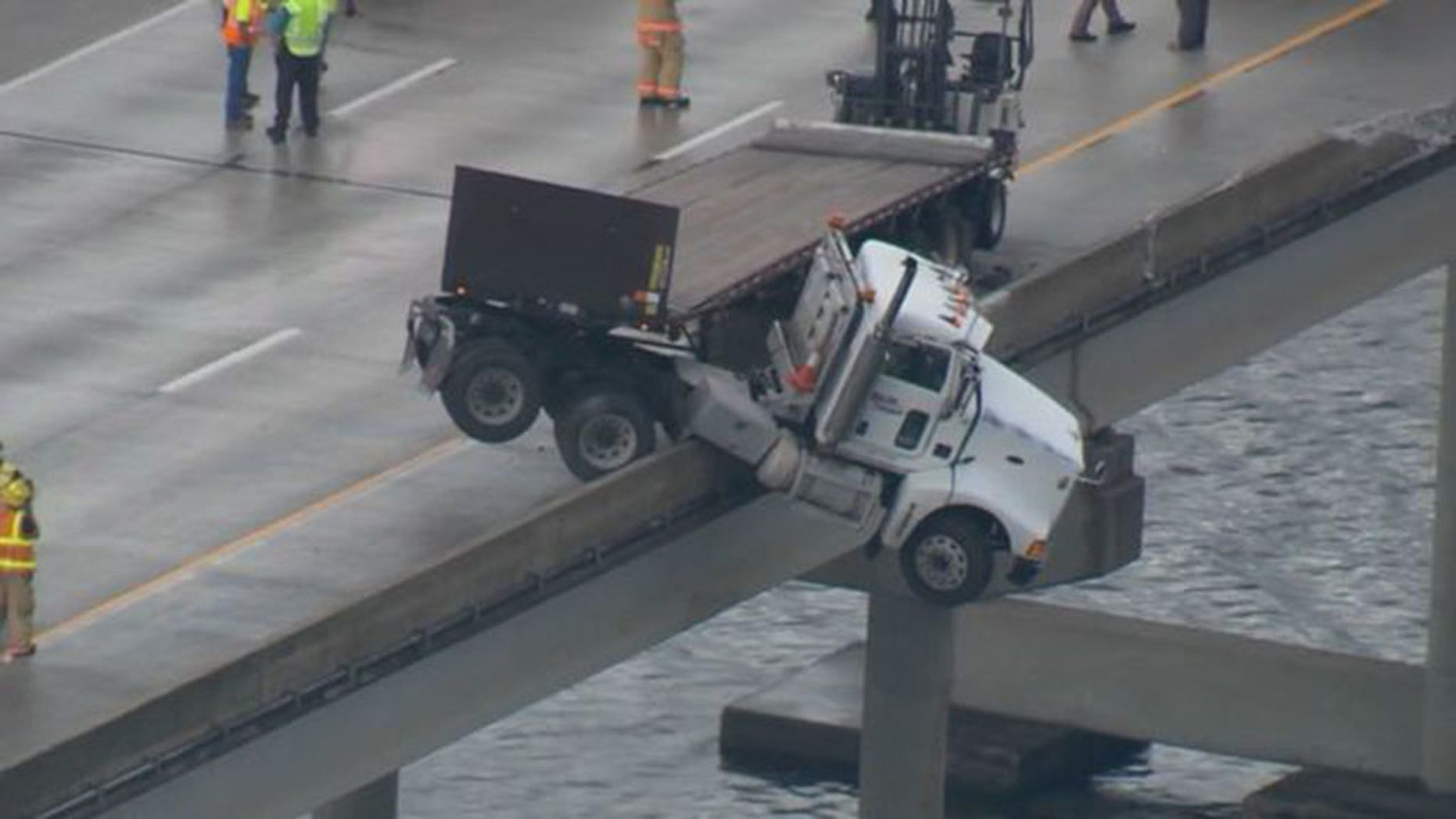 A semi-truck was suspended halfway over the side of a Florida overpass.