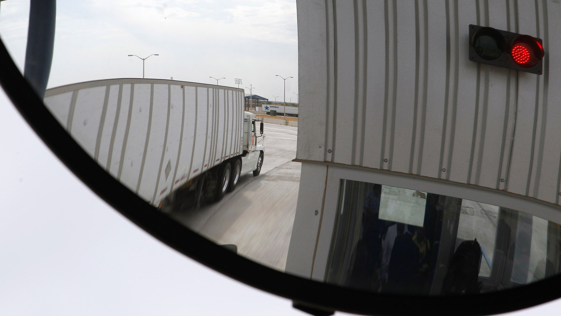 In this May 6, 2011 file photo, a trucker, seen in a security mirror, passes through an inspection booth for commercial traffic heading north into the U.S. from Mexico at the World Trade Bridge in Laredo, Texas.