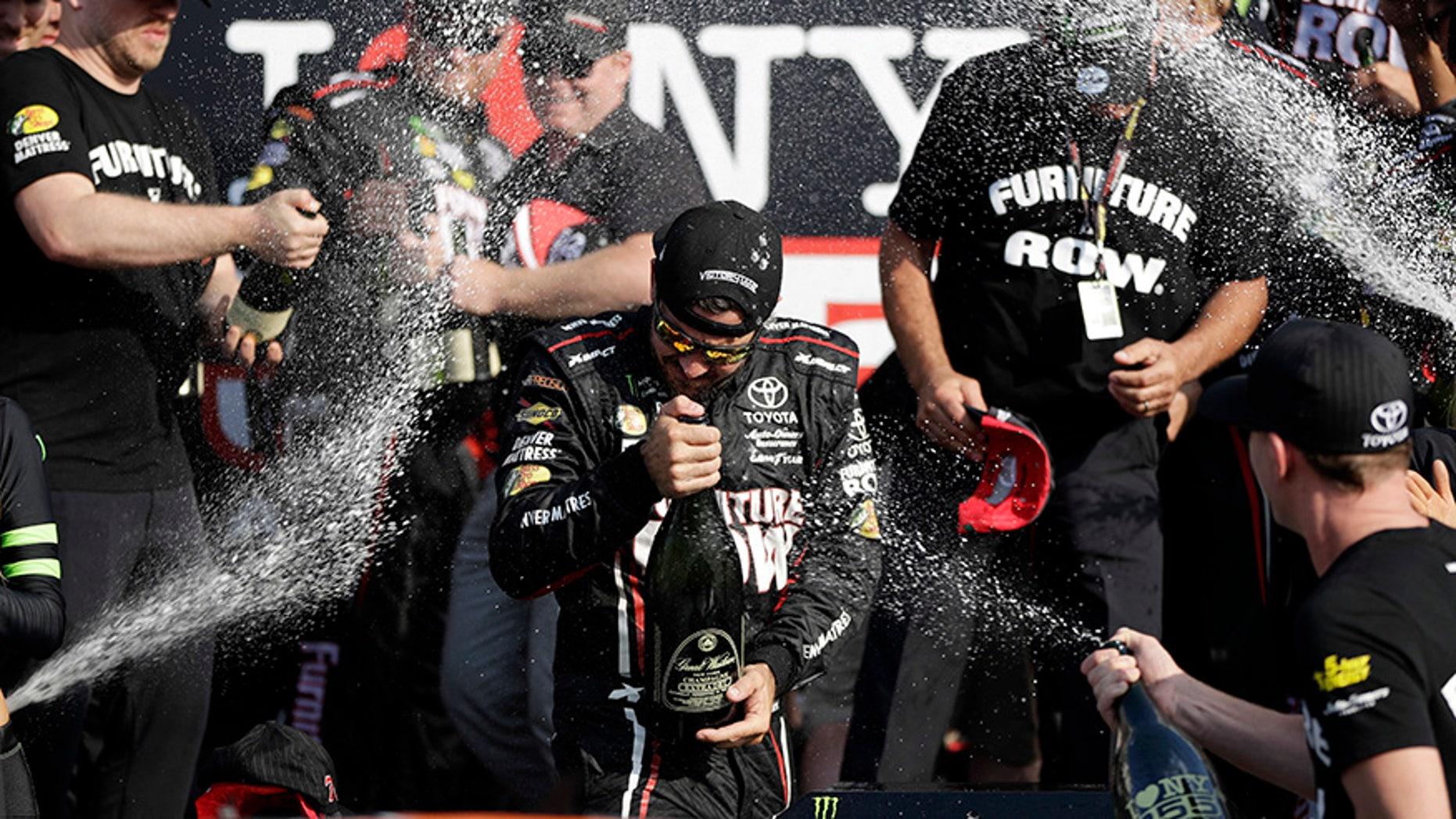 Martin Truex Jr., center, celebrates after winning the NASCAR Cup Series auto race, Sunday, Aug. 6, 2017, in Watkins Glen, N.Y. (AP Photo/Matt Slocum)