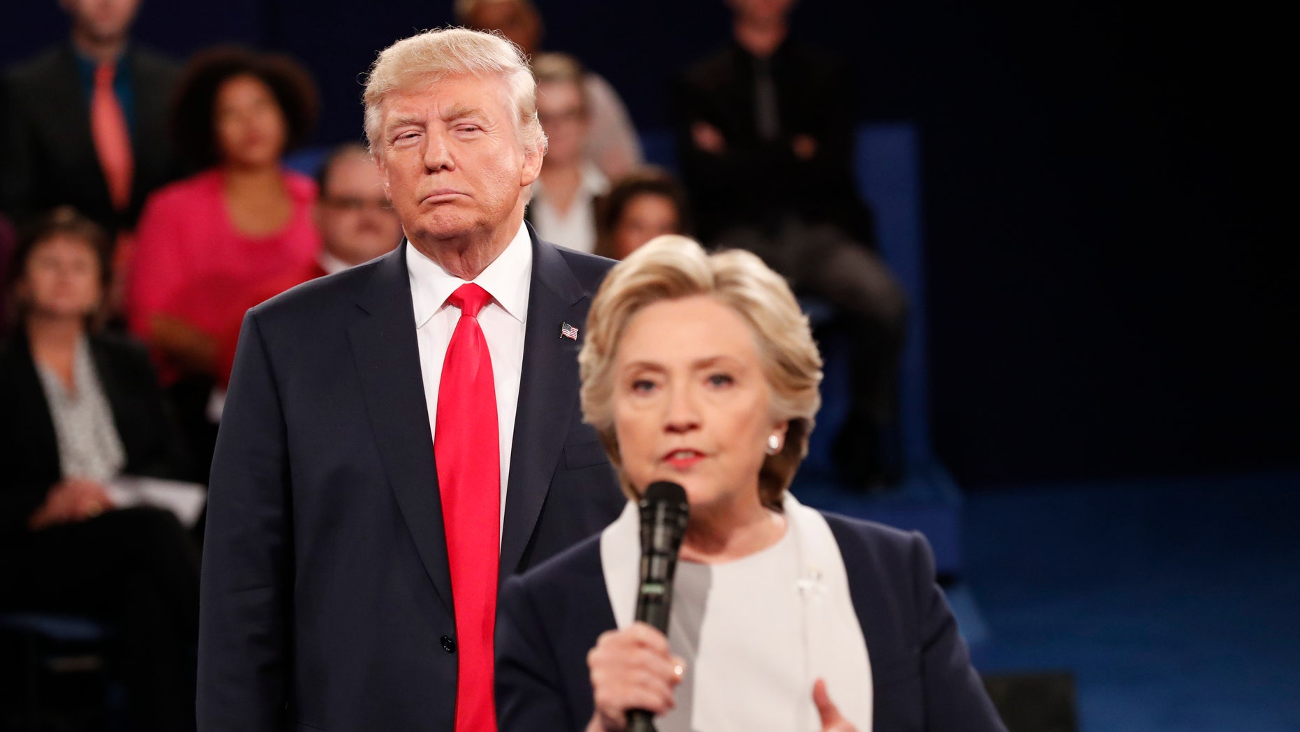 Republican U.S. presidential nominee Donald Trump listens as Democratic nominee Hillary Clinton answers a question from the audience during their presidential town hall debate at Washington University in St. Louis, Missouri, U.S., October 9, 2016. REUTERS/Rick Wilking - RTSRIR9