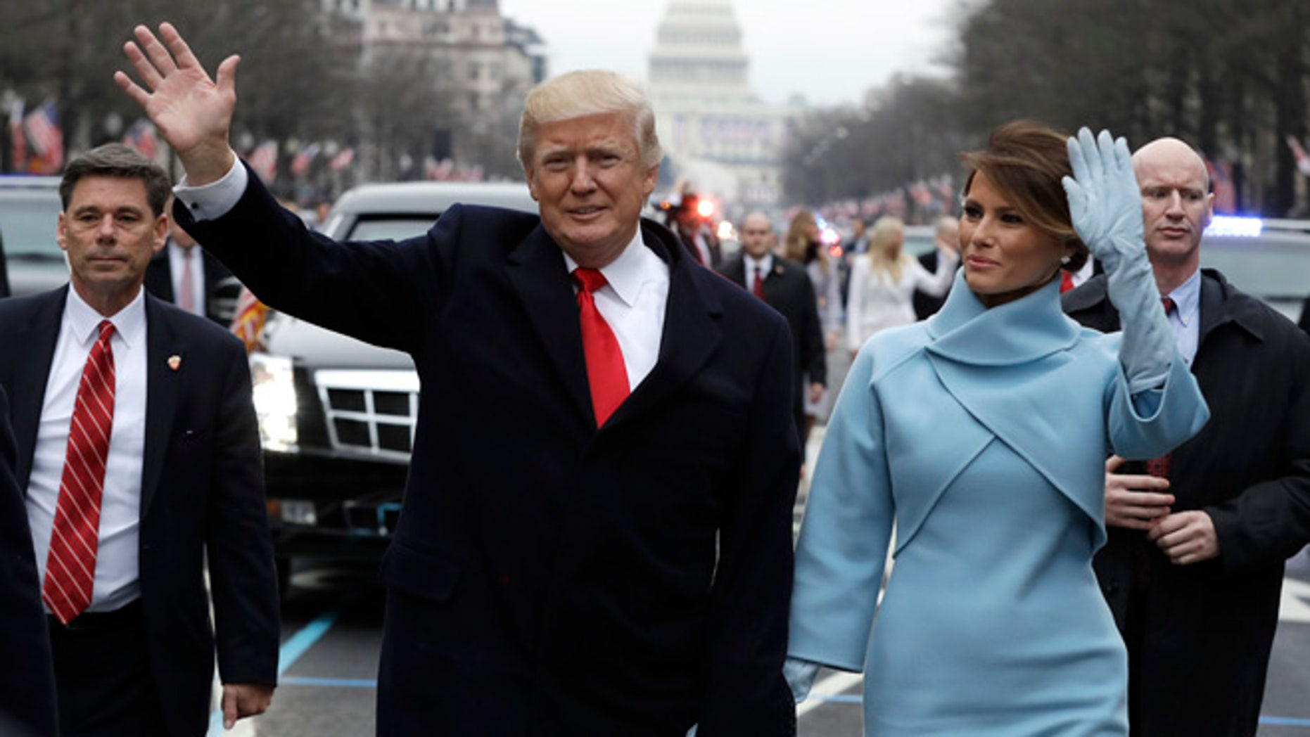 President Donald Trump waves as he walks with first lady Melania Trump during the inauguration parade on Pennsylvania Avenue in Washington, Friday, Jan. 20, 2016. (AP Photo/Evan Vucci, Pool)