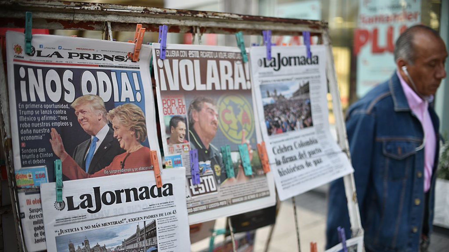 A man walks by a newsstand displaying front pages showing images of US presidential candidates debate and Colombia's peace agreement, in Mexico City on September 27, 2016. (Photo credit: YURI CORTEZ/AFP/Getty Images)