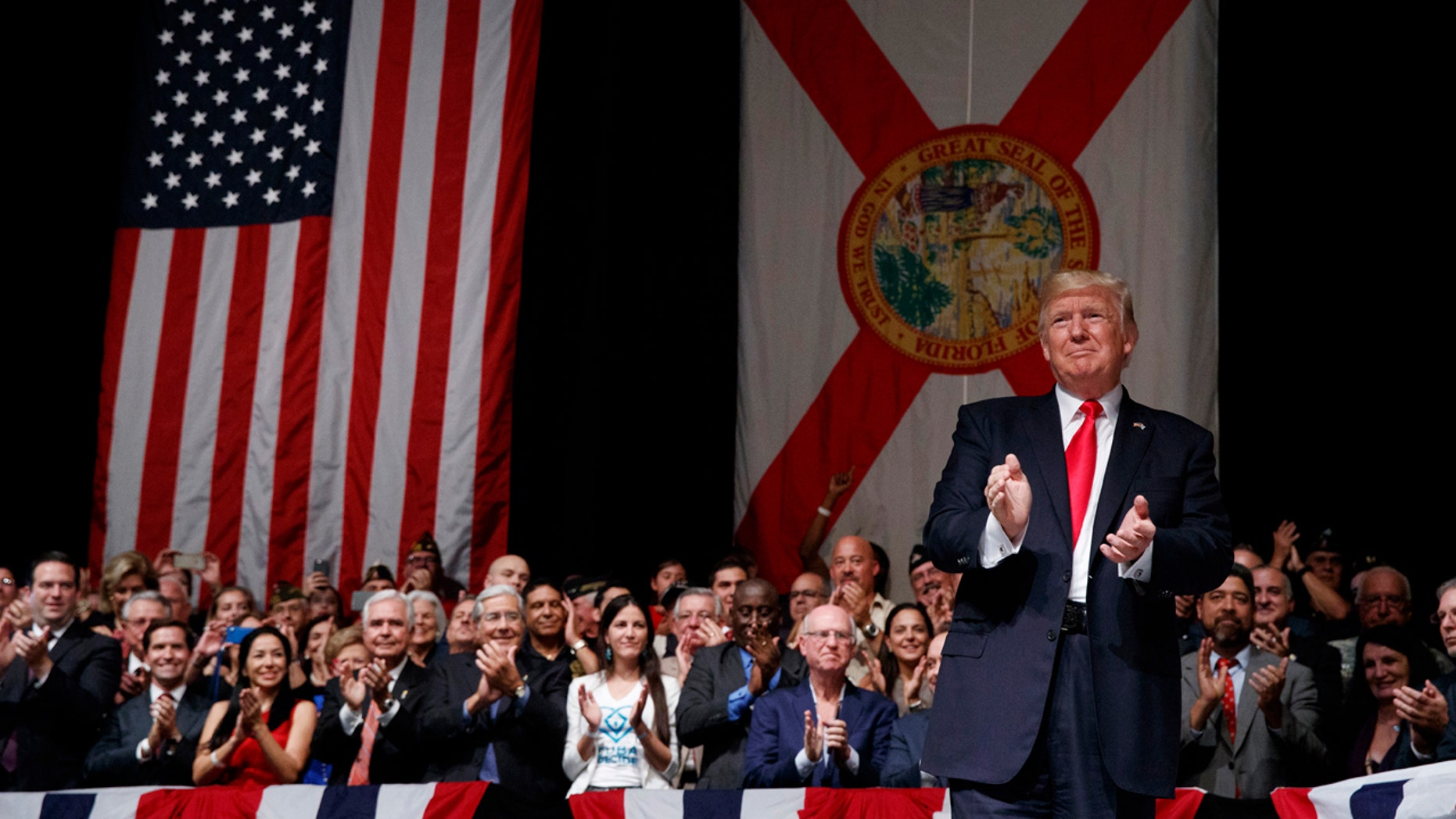 June 16, 2017: President Donald Trump applauds as he arrives to speak about Cuba policy in Miami. The president announced changes to Obama-era Cuba policy, and challenged the Castro government to negotiate a better deal.