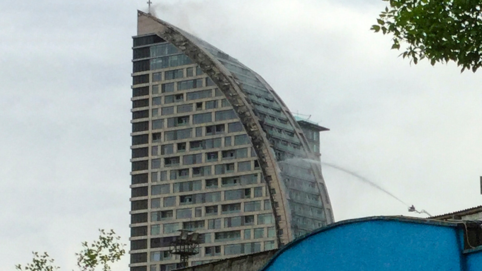 Azerbaijani firefighters work at the scene of the Trump-branded building in Baku, Azerbaijan, Saturday.