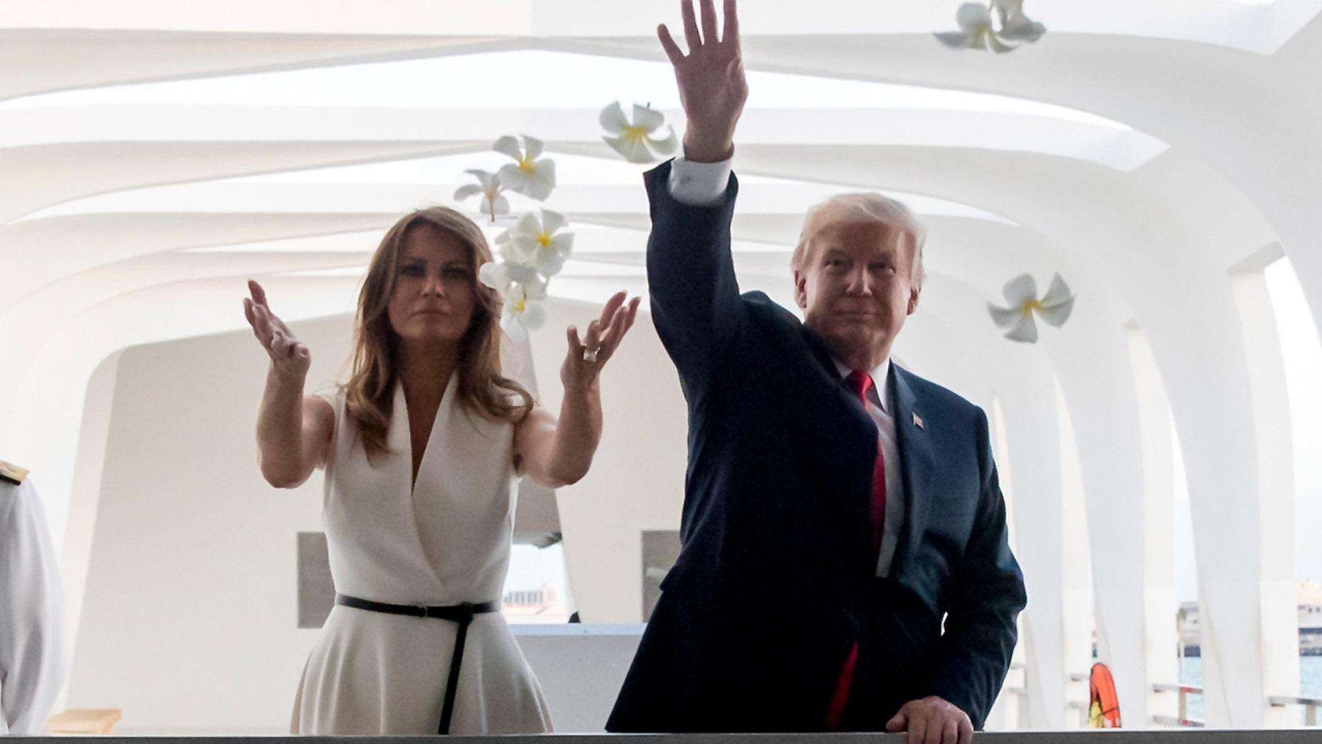 President Donald Trump and first lady Melania Trump toss flower petals while visiting the USS Arizona Memorial at Pearl Harbor, Hawaii, Nov. 3, 2017.