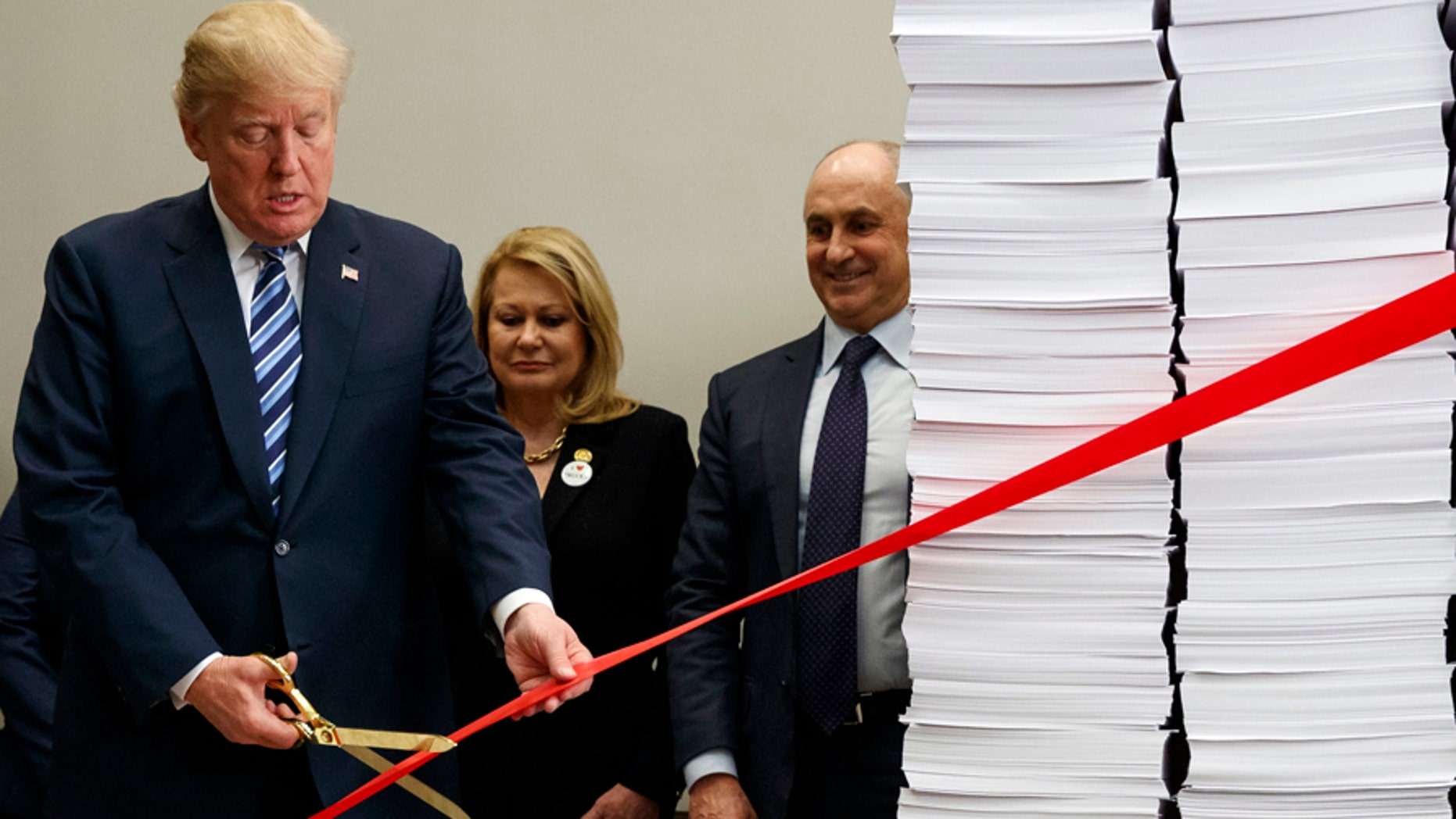"""President Donald Trump cuts a ribbon during an event on federal regulations in the Roosevelt Room of the White House, Thursday, Dec. 14, 2017, in Washington. """"Let's cut the red tape, let's set free our dreams,"""" Trump said as he symbolically cut a ribbon on stacks of paper representing the size of the regulatory code. (AP Photo/Evan Vucci)"""