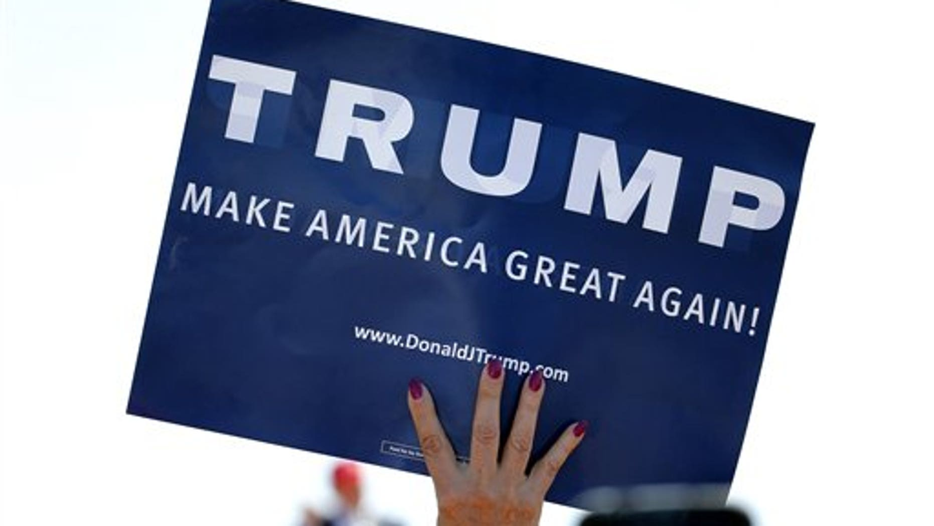 In this March 19, 2016 file photo, a supporter holds a sign as Republican presidential candidate Donald Trump speaks during a campaign rally in Fountain Hills, Ariz.  (AP Photo/Matt York)