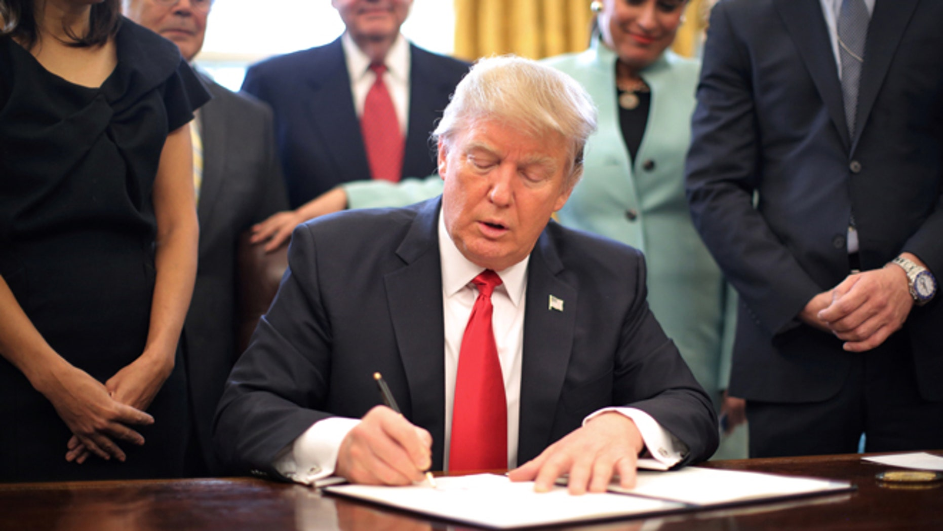 FILE -- January 30, 2017: President Donald Trump signs an executive order cutting regulations, accompanied by small business leaders at the Oval Office of the White House in Washington.