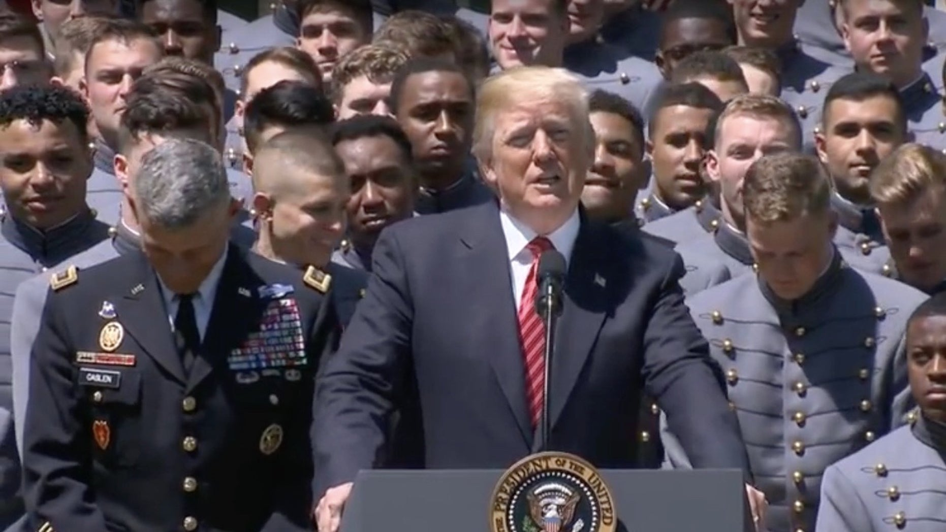 President Donald Trump presents the Commander-in-Chief's Trophy to the Army Black Knights college football team during a ceremony at the White House on May 1, 2018.