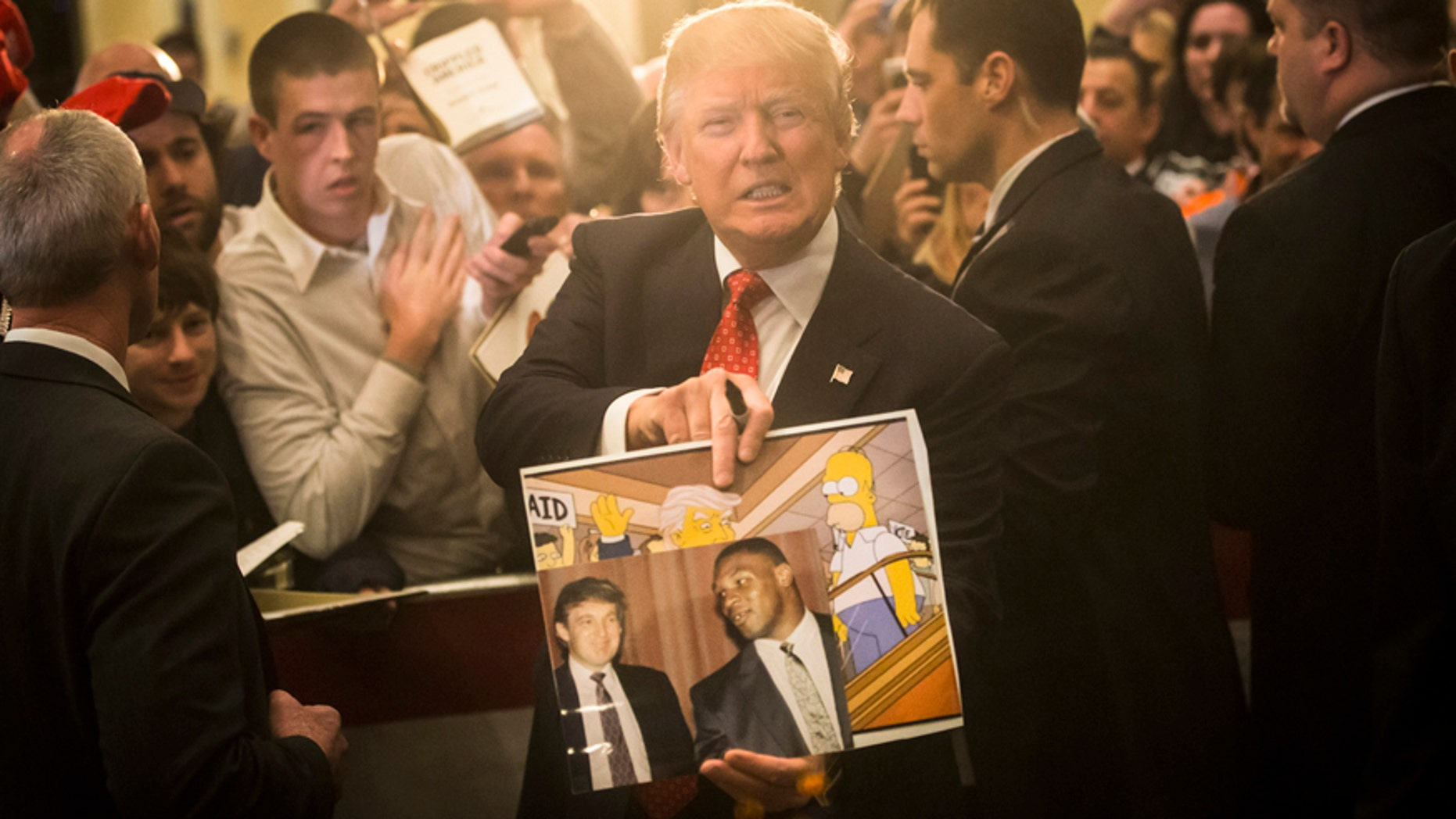 """In this Jan. 29, 2016, file photo, Republican presidential candidate Donald Trump holds depictions of himself on, """"The Simpsons"""" and a photo with boxer Mike Tyson, given to him by an attendee during a campaign stop at the Radisson Hotel in Nashua, N.H. """"The Simpsons"""" released a short online clip on April 26, 2017, mocking President Donald Trump ahead of his 100th day in office."""