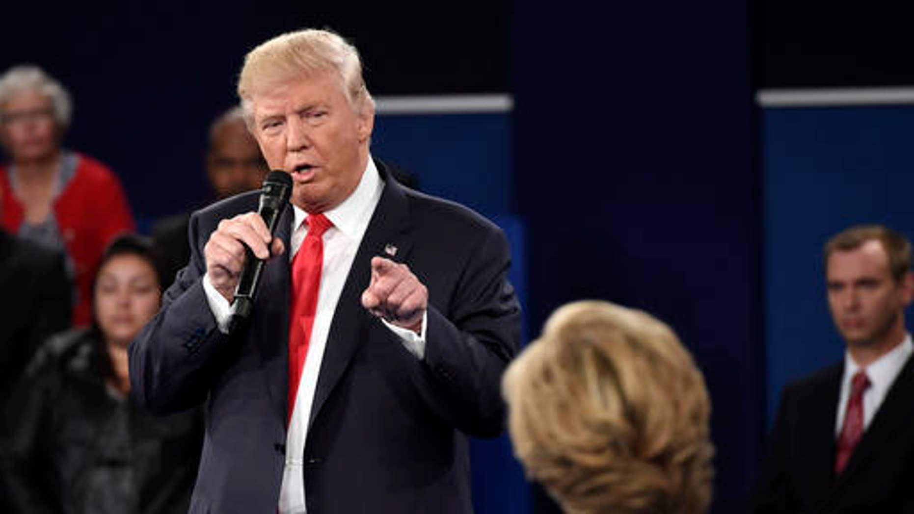 FILE - Republican presidential nominee Donald Trump points at Democratic presidential nominee Hillary Clinton as he speaks during the second presidential debate at Washington University in St. Louis, Sunday, Oct. 9, 2016.