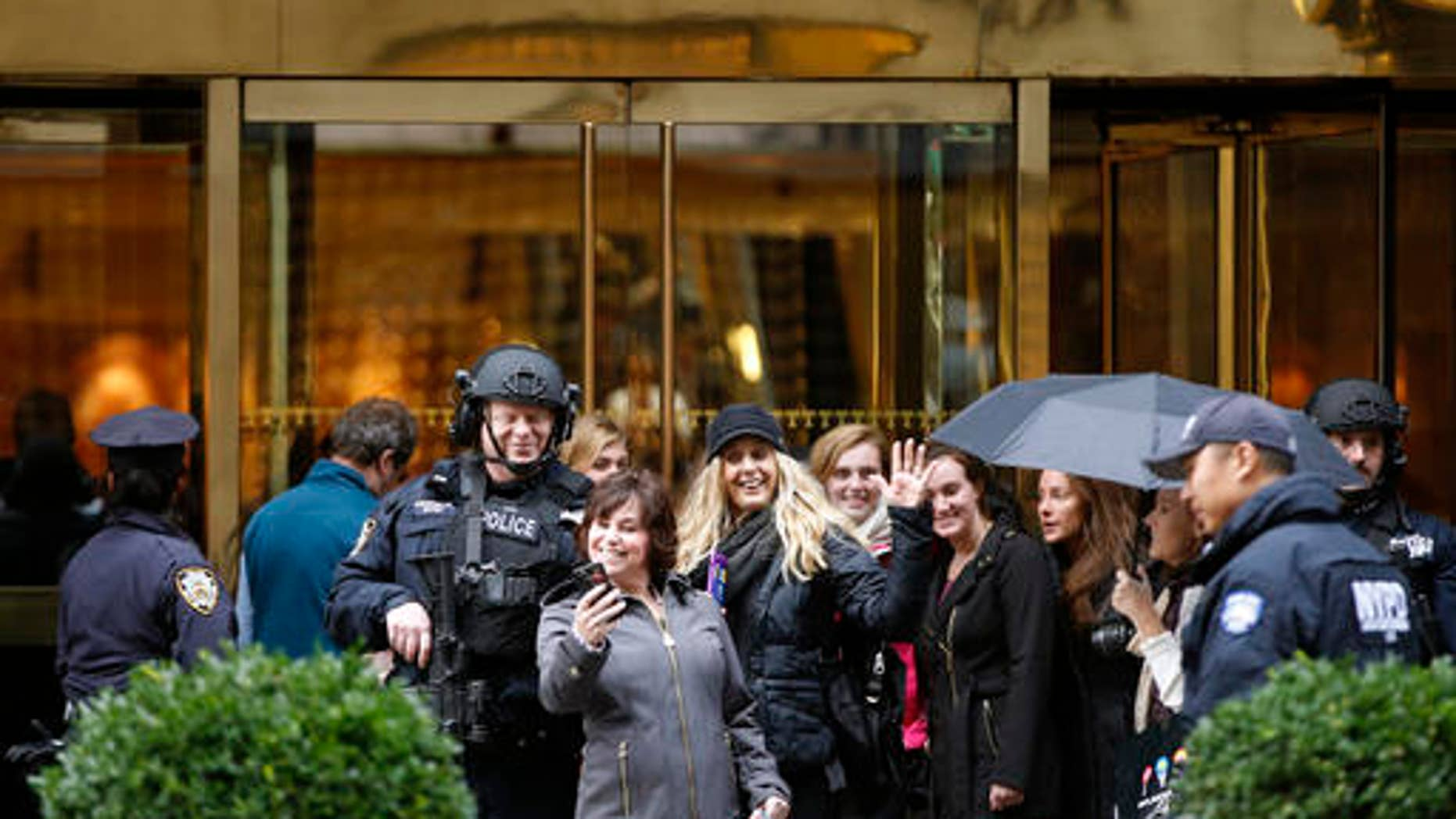 Passersby stop for a selfie with a heavily-armed New York City police officer at the main, Fifth Avenue entrance to Trump Tower, Tuesday, Nov. 15, 2016, in New York. For nearly the entire week since he became president-elect, Donald Trump has been holed up in the tower, his gilded New York skyscraper.