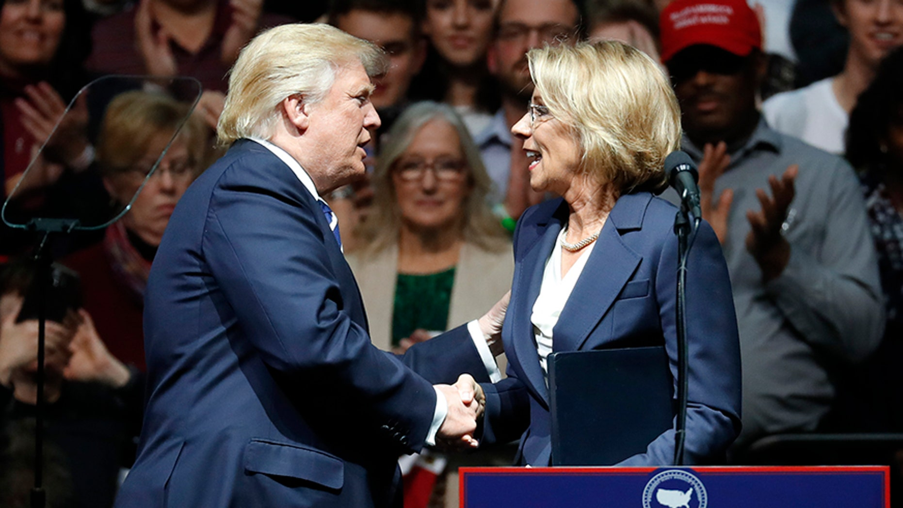President-elect Donald Trump shakes hands with his pick for Education Secretary Betsy DeVos during a rally, in Grand Rapids, Mich., Friday, Dec. 9, 2016.