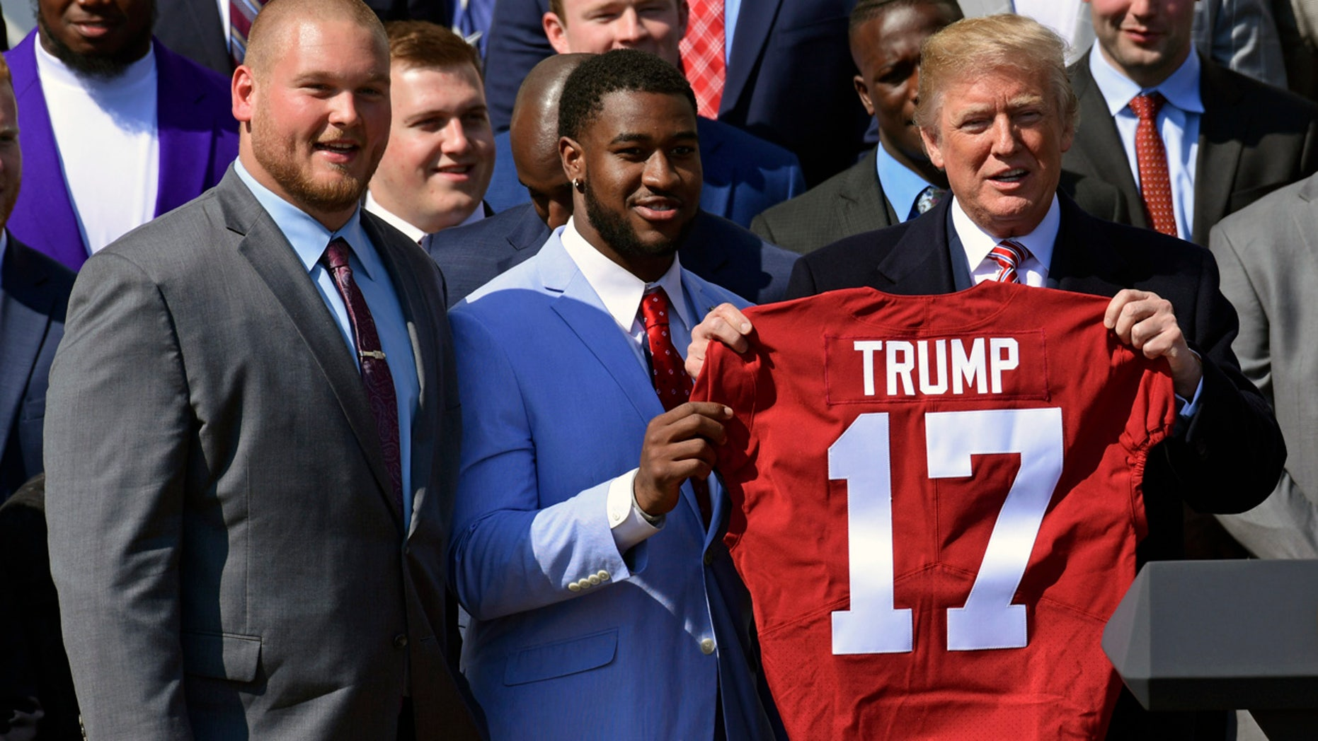 President Trump was presented with a jersey by Alabama team captains Bradley Bozeman, left, and Rashaan Evans on the South Lawn of the White House Tuesday.