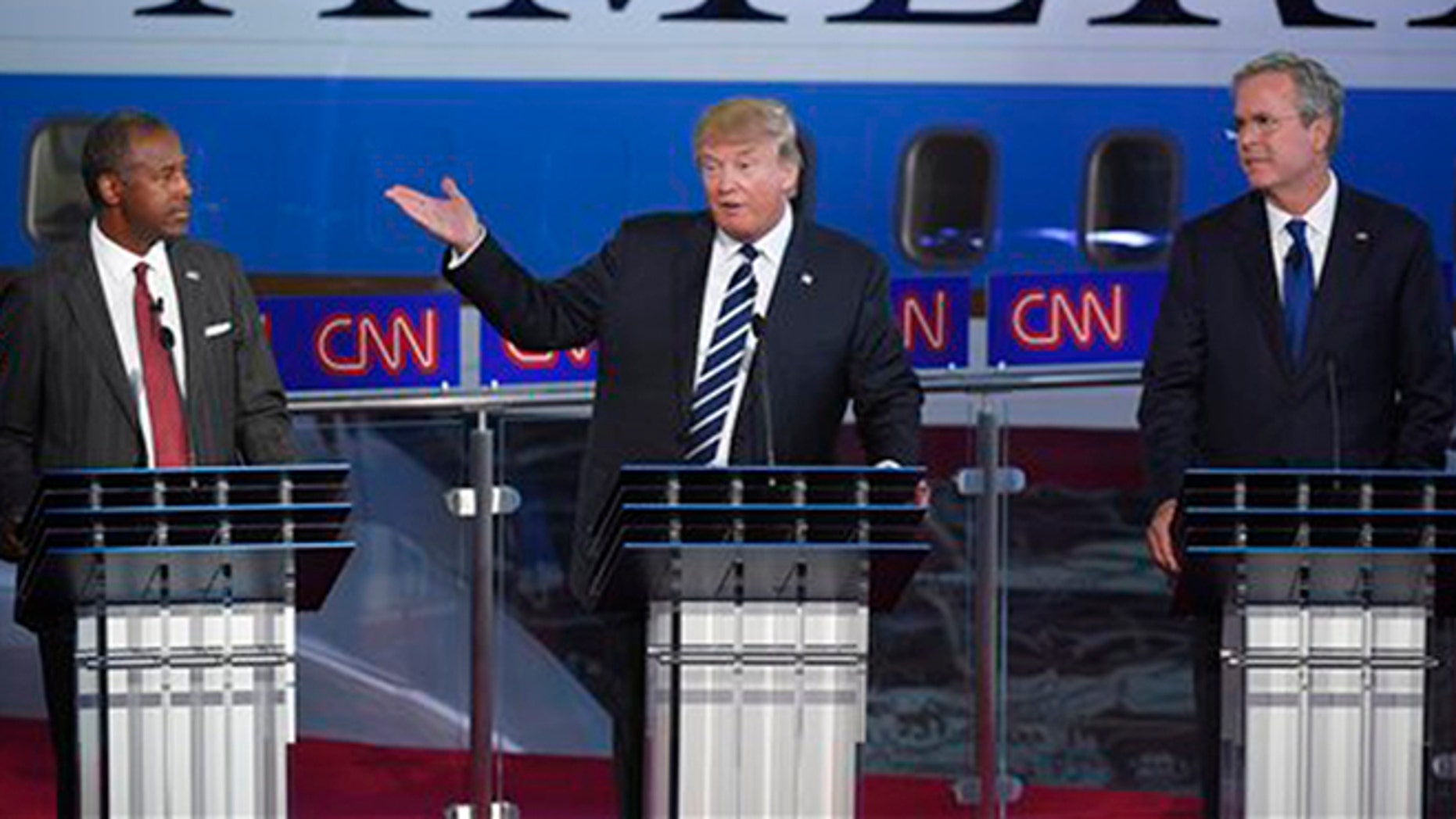 Republican presidential candidate, businessman Donald Trump, center, speaks as Ben Carson, left, and Jeb Bush, look on during the CNN Republican presidential debate at the Ronald Reagan Presidential Library and Museum on Wednesday, Sept. 16, 2015, in Simi Valley, Calif. (AP Photo/Mark J. Terrill)