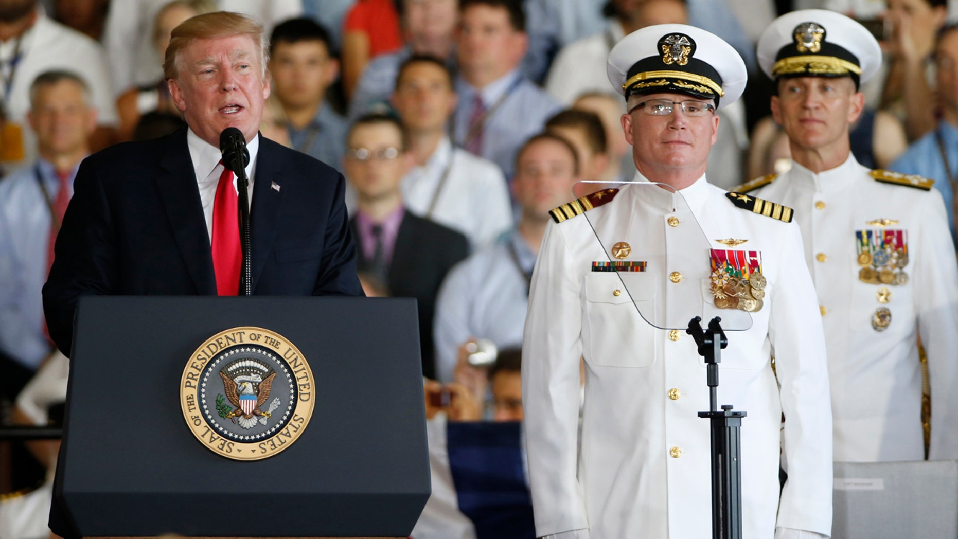 President Donald Trump, left, puts the USS Gerald R Ford into commission as Ships commander Capt. Richard McCormack, front right, listens in Norfolk, Va. Saturday.