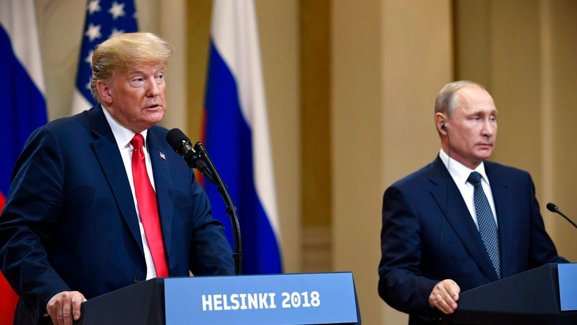 U.S. President Donald Trump speaks as Russian President Vladimir Putin listens during a join press conference at the Presidential Palace in Helsinki, Finland, Monday, July 16, 2018. (Antti Aimo-Koivisto/Lehtikuva via AP)