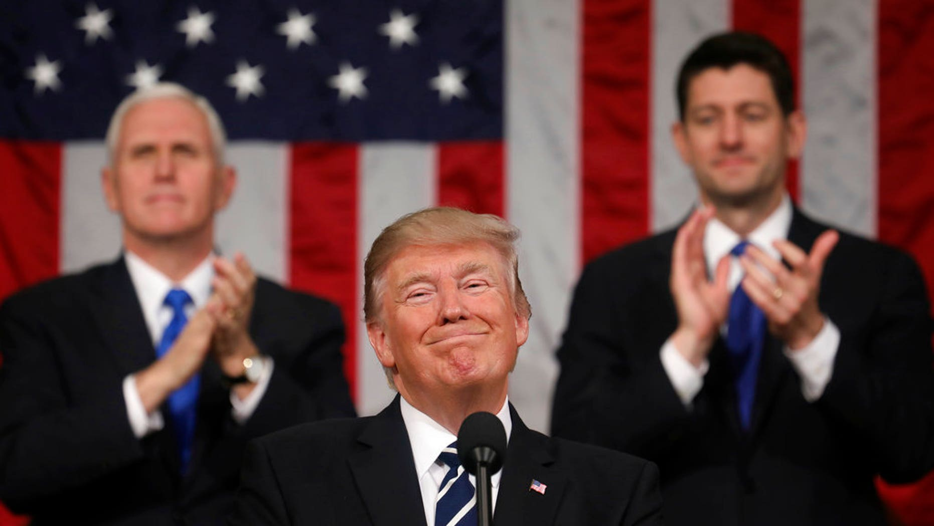 FILE - In this Feb. 28, 2017, file photo, President Donald Trump addresses a joint session of Congress on Capitol Hill in Washington, as Vice President Mike Pence and House Speaker Paul Ryan of Wis., applaud. President Trump's first state of the union speech will carry more suspense than most. (Jim Lo Scalzo/Pool Image via AP, File)