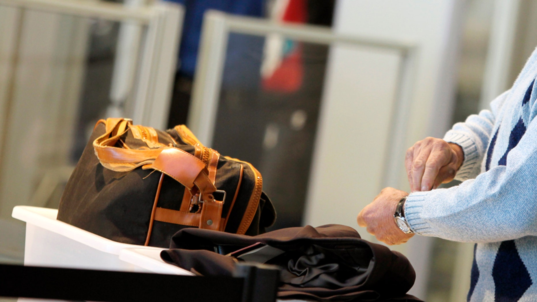 An airline passenger removes his watch before being screened at a security checkpoint.