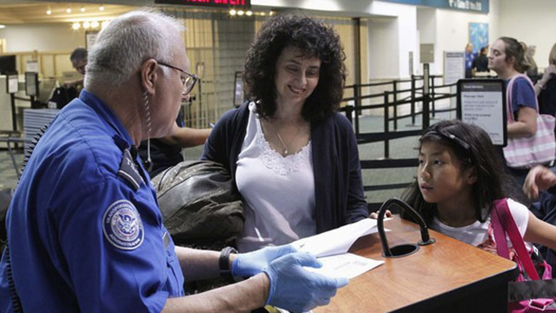 Passengers provide documents at a security checkpoint operated by the Transportation Security Administration at Fort Lauderdale-Hollywood International Airport in Fort Lauderdale, Fla., Nov. 23, 2010.