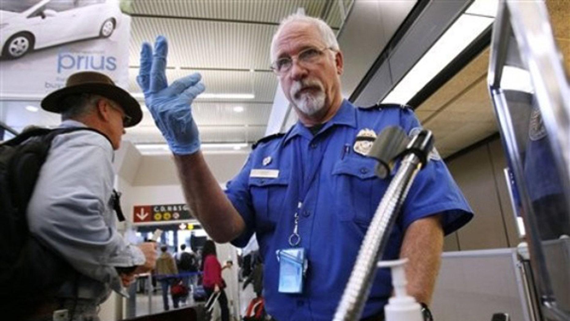 TSA officer Robert Howard signals an airline passenger forward at a security check-point at Seattle-Tacoma International Airport  Jan. 4. (AP Photo)