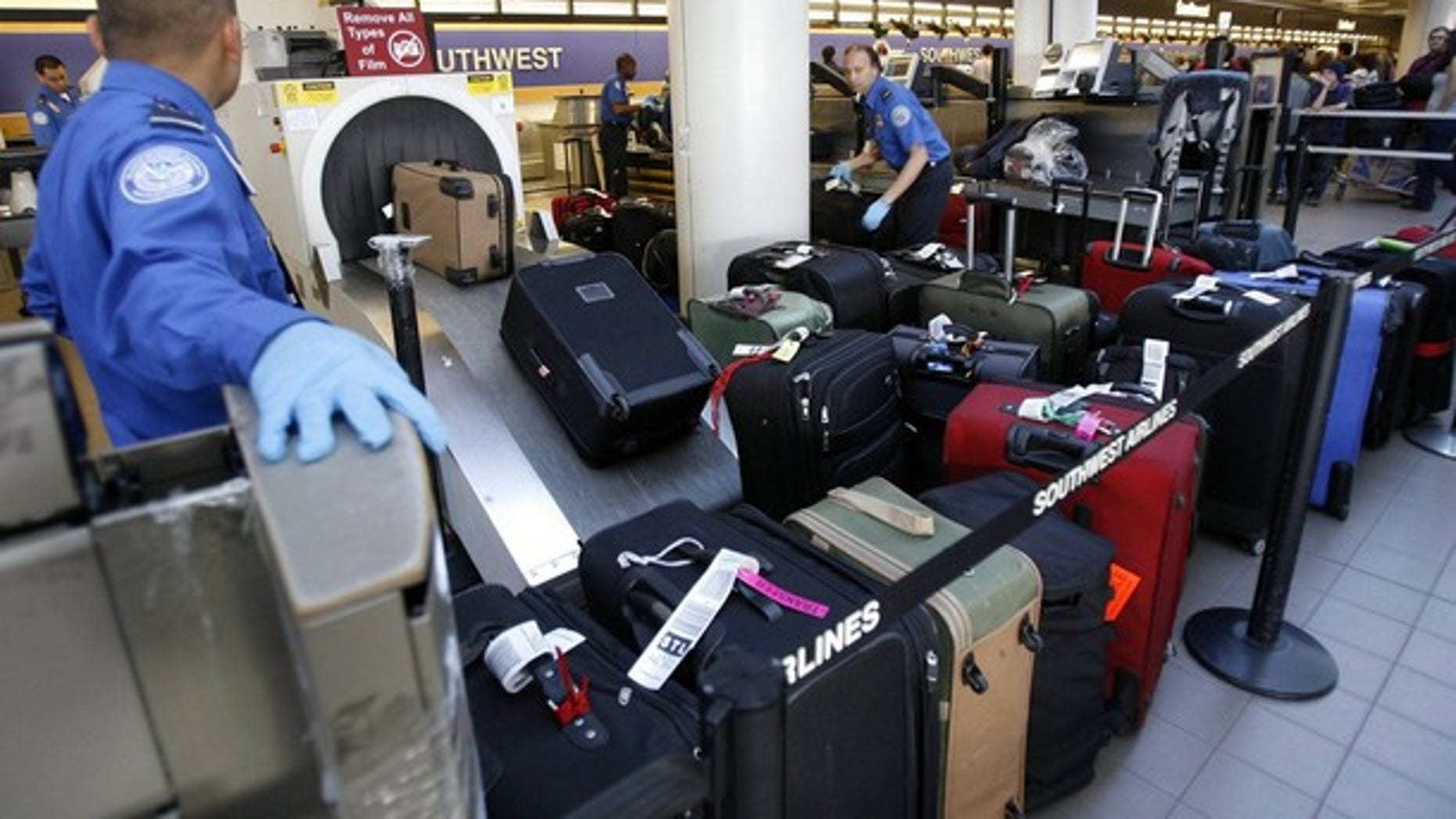 Transportation Security Administration officers put passengers' suitcases through an X-ray machine at Los Angeles International Airport Dec. 29. (Reuters Photo)