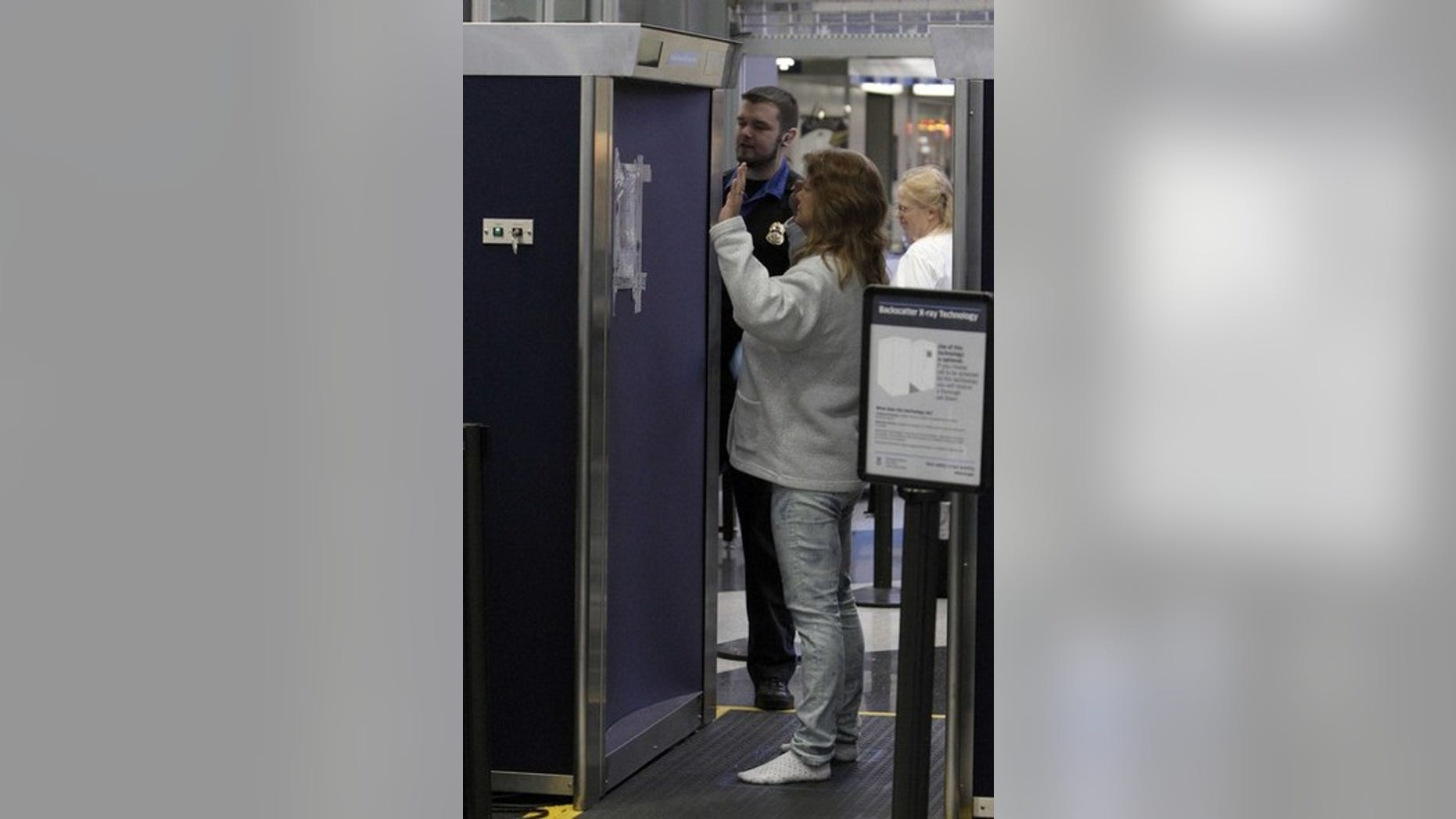 A passenger is examined by a full-body scanner at a Transportation Security Administration screening check-point at O'Hare International airport in Chicago November 24, 2010. The TSA has been flooded with complaints concerning what some term their law-enforcement style pat downs of passengers opting-out of full-body scans.