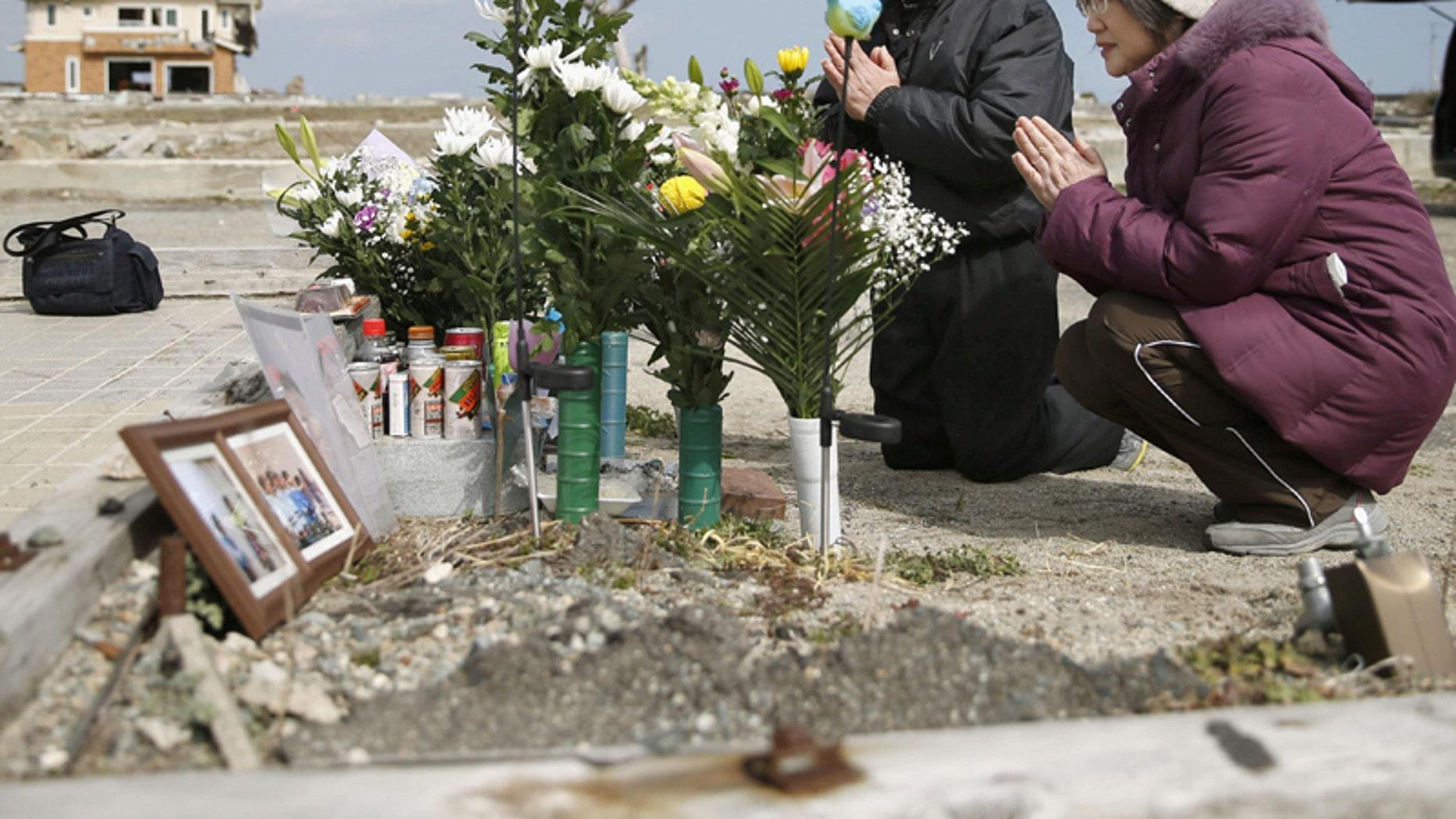 March 11, 2016: Tsutoshi Yoshida and his wife Seiko pray for their daughter who was killed by the 2011 tsunami, in Namie, Fukushima, northern Japan. (AP)