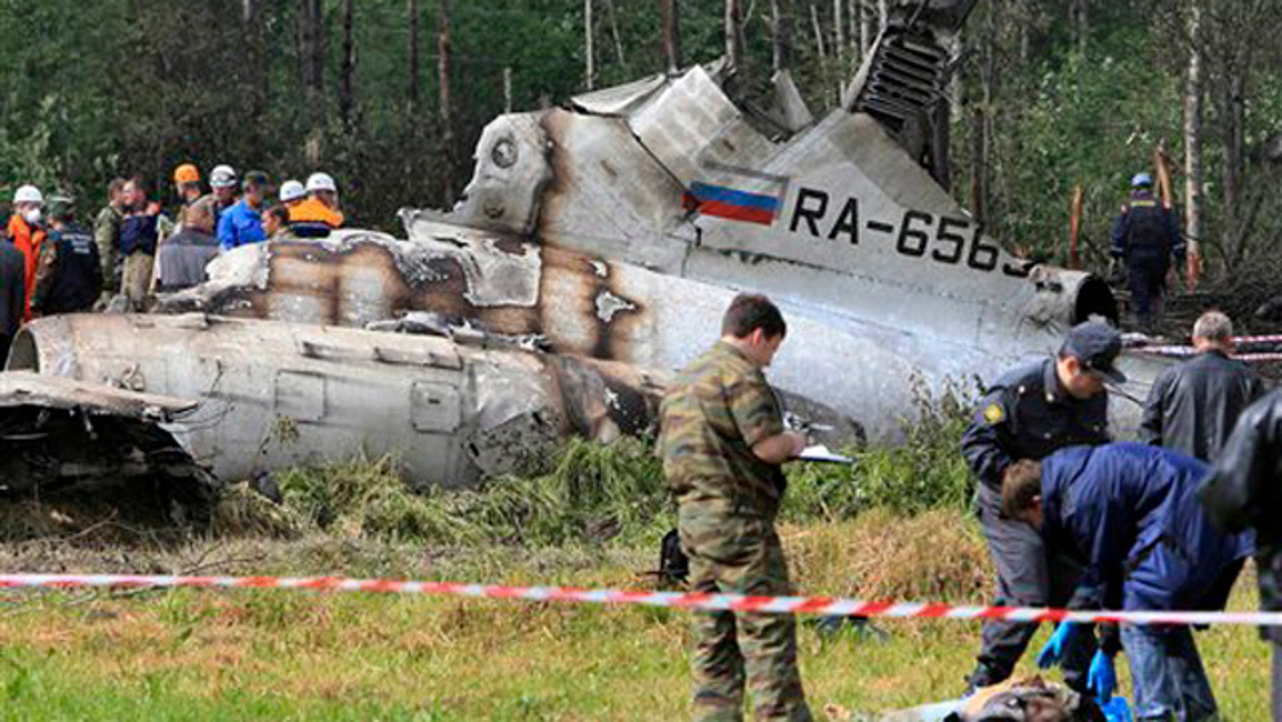 In this Tuesday, June 21, 2011 file photo, forensic experts examine a body near a wreckage of Tu-134 plane, belonging to the RusAir airline, near the city of Petrozavodsk, Russia.