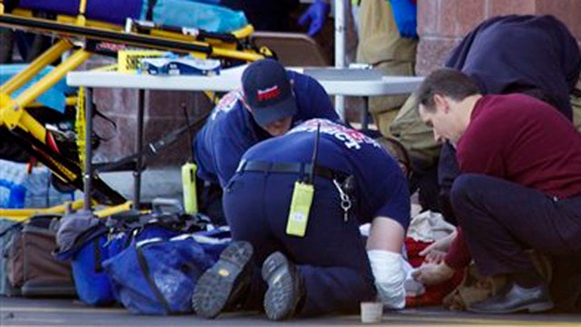 Emergency personnel attend to a shooting victim outside a shopping center in Tucson, Ariz., on Jan. 8.