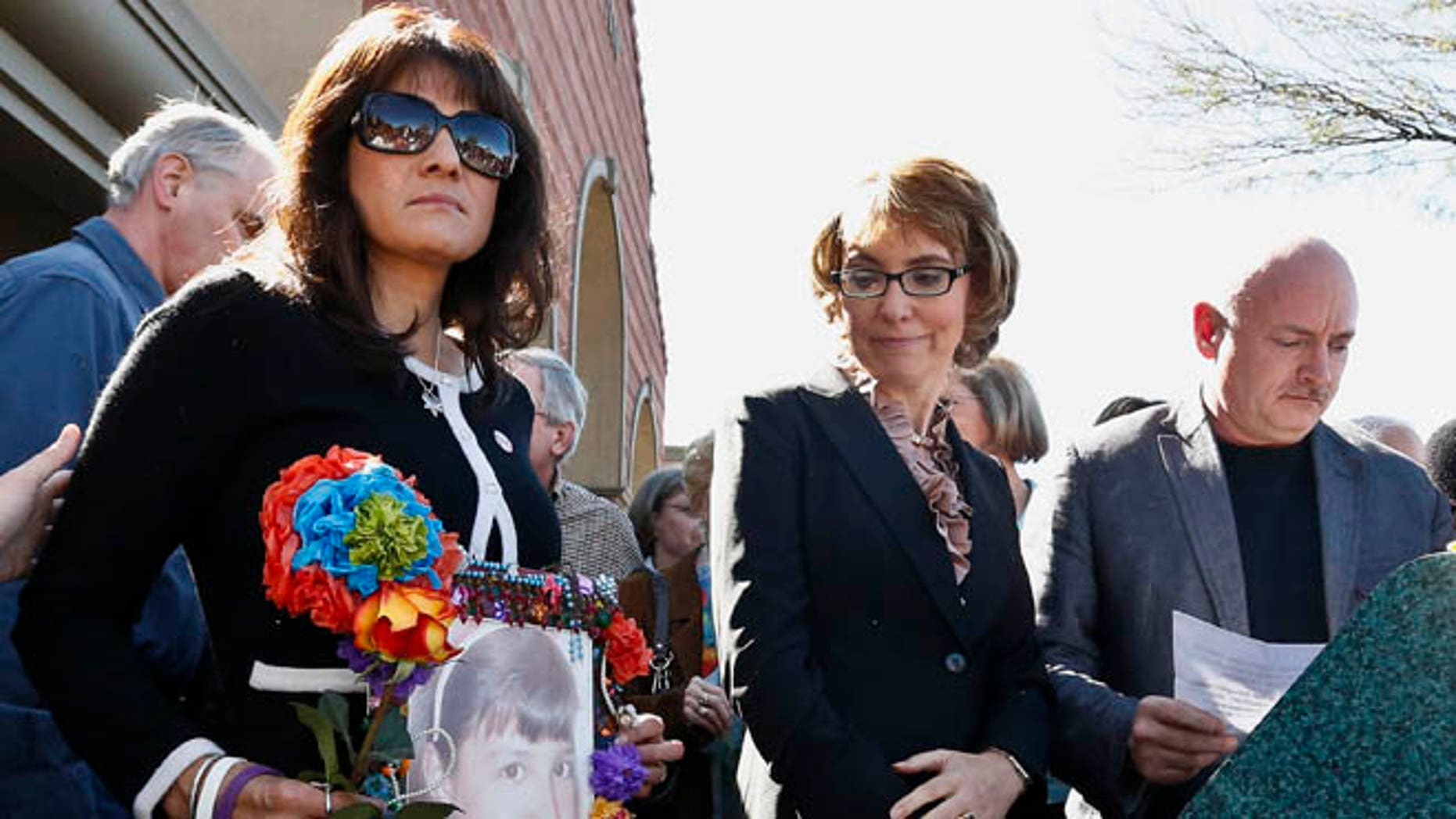 March 6, 2013: In this file photo, former Rep. Gabrielle Giffords, center, looks at a photo of Christina-Taylor Green, as it is held by her mother Roxanna Green, left, as Giffords' husband Mark Kelly prepares to speak at the site of a shooting that left her critically wounded, and many others killed in Phoenix.