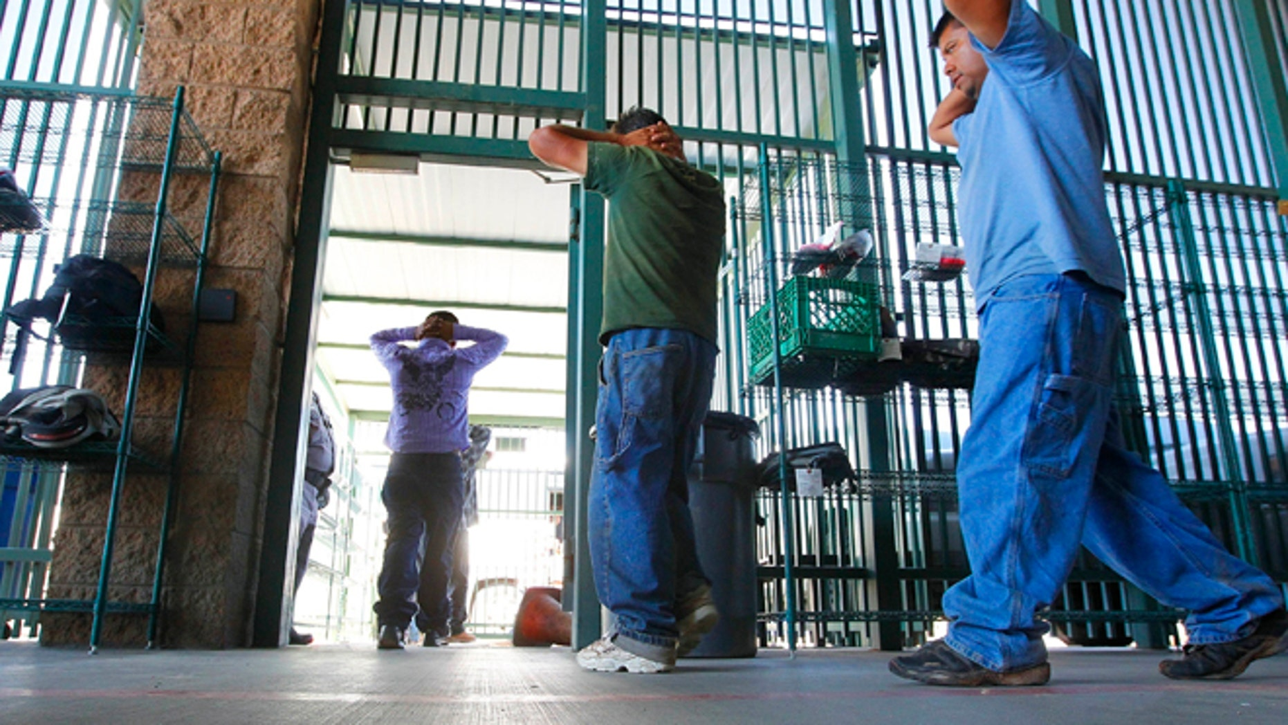 In this Aug. 9, 2012, file photo, suspected illegal immigrants are transferred out of the holding area after being processed at the Tucson Sector of the U.S. Customs and Border Protection headquarters in Tucson, Ariz.