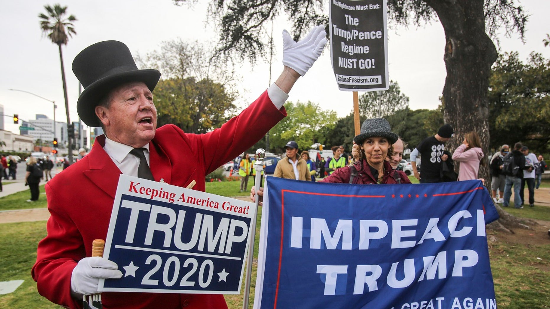 Gregg Donovan, left, supporter of President Donald Trump holds a sign during a rally against a visit by President Donald Trump, March 13, 2018.