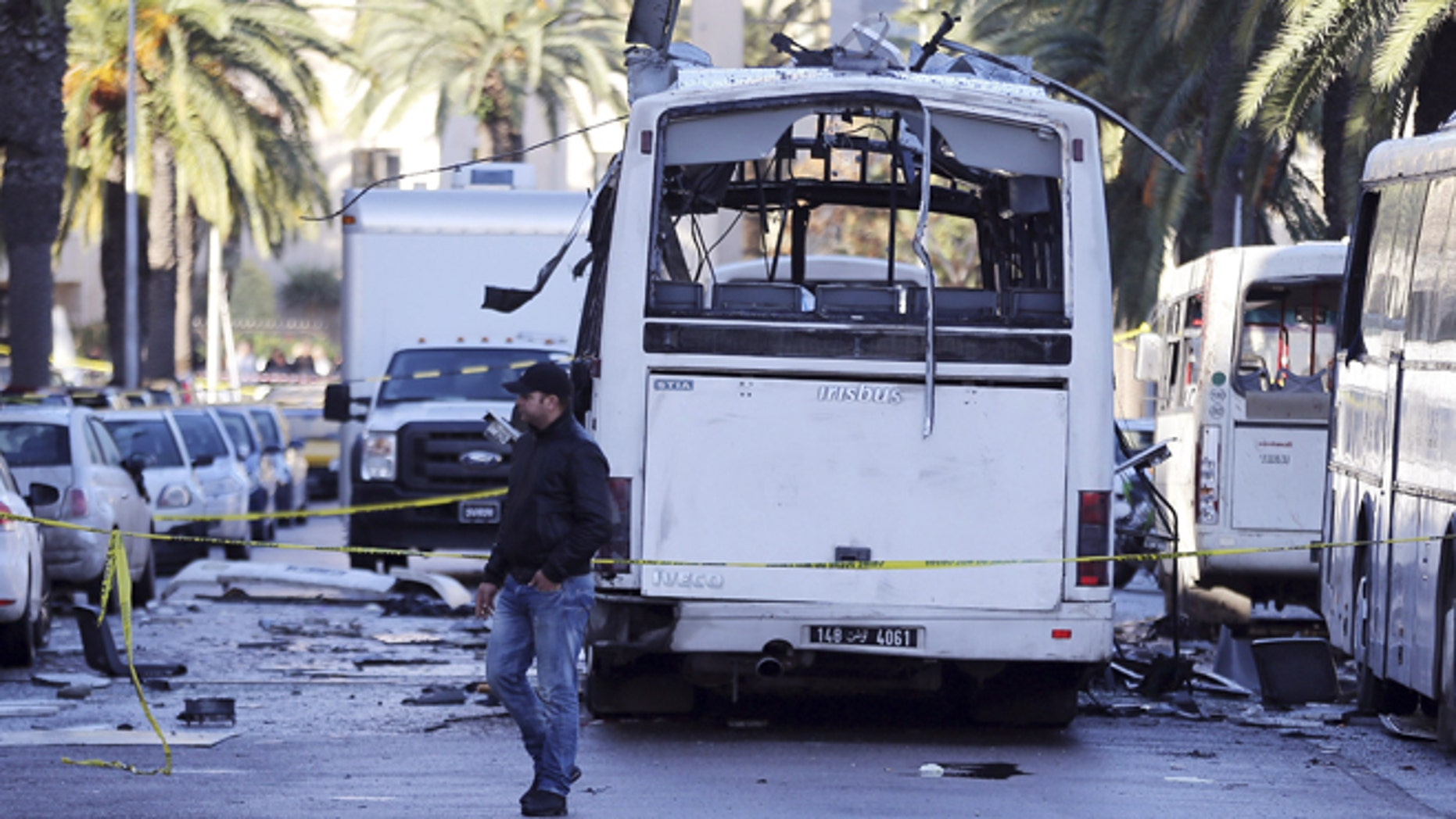 Nov. 25, 2015: A man walks past the bus that exploded Tuesday in Tunis.