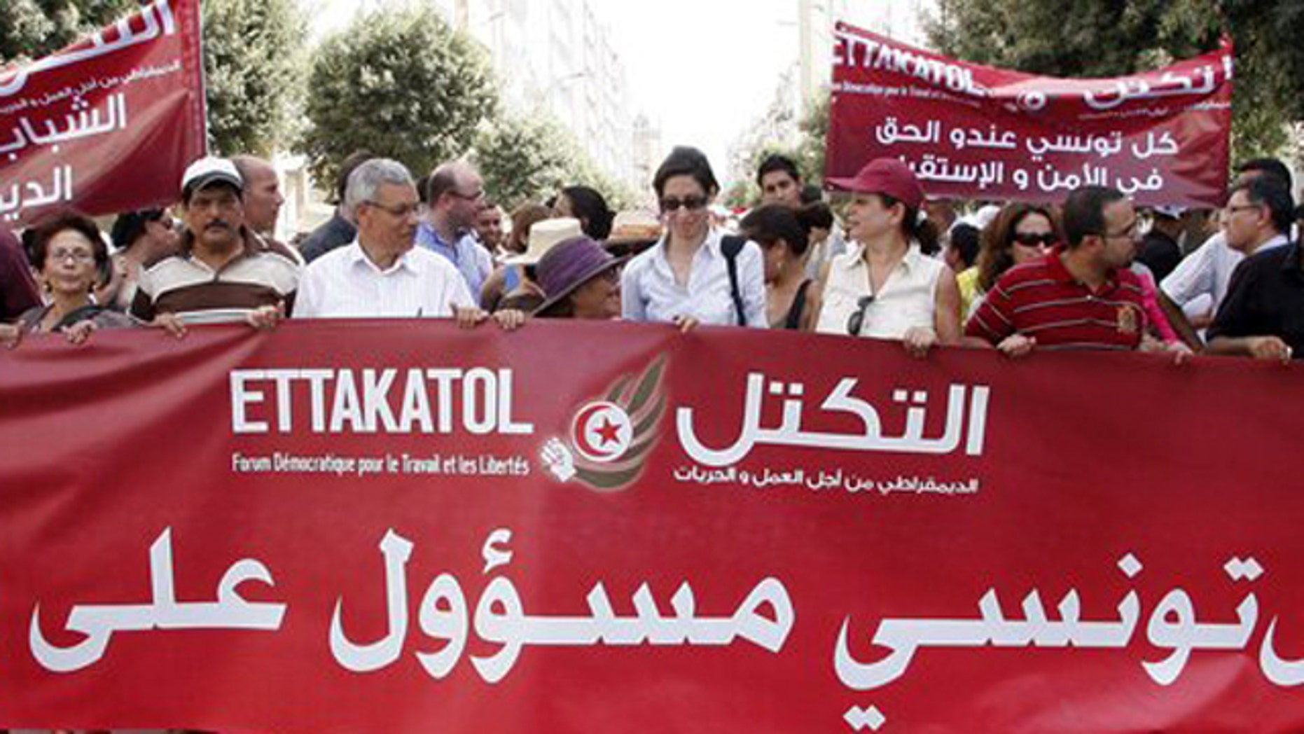 """Demonstrators from a dozen of political parties hold a banner reading """"Each Tunisian is responsible for his country"""" during a march against violence in Tunis , Thursday, July 21, 2011 as Tunisia prepares for landmark Oct. 23 elections for a body meant to write a new constitution. Banner at right behind reads: Any Tunisian has the right to security."""