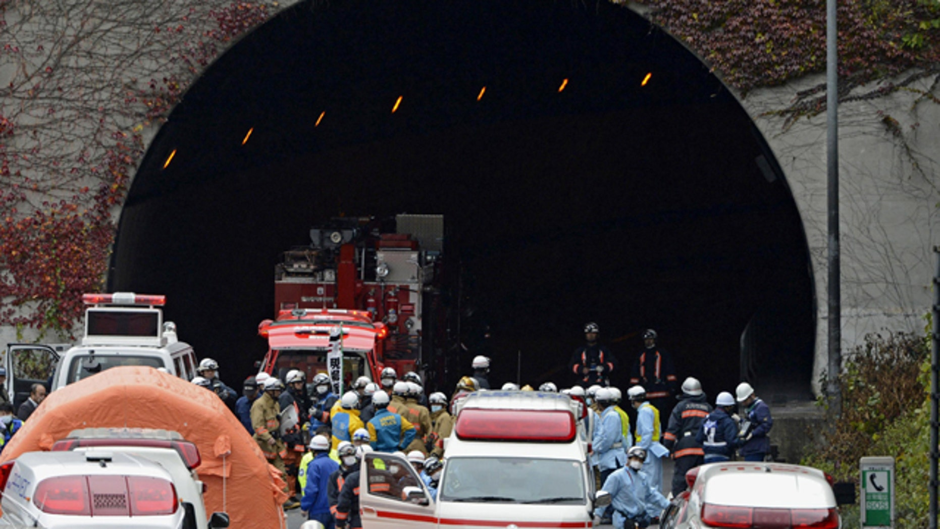 Dec. 2, 2012: Police officers and firefighters gather at the exit of the Sasago Tunnel on the Chuo Expressway in Otsuki, Yamanashi Prefecture, central Japan.