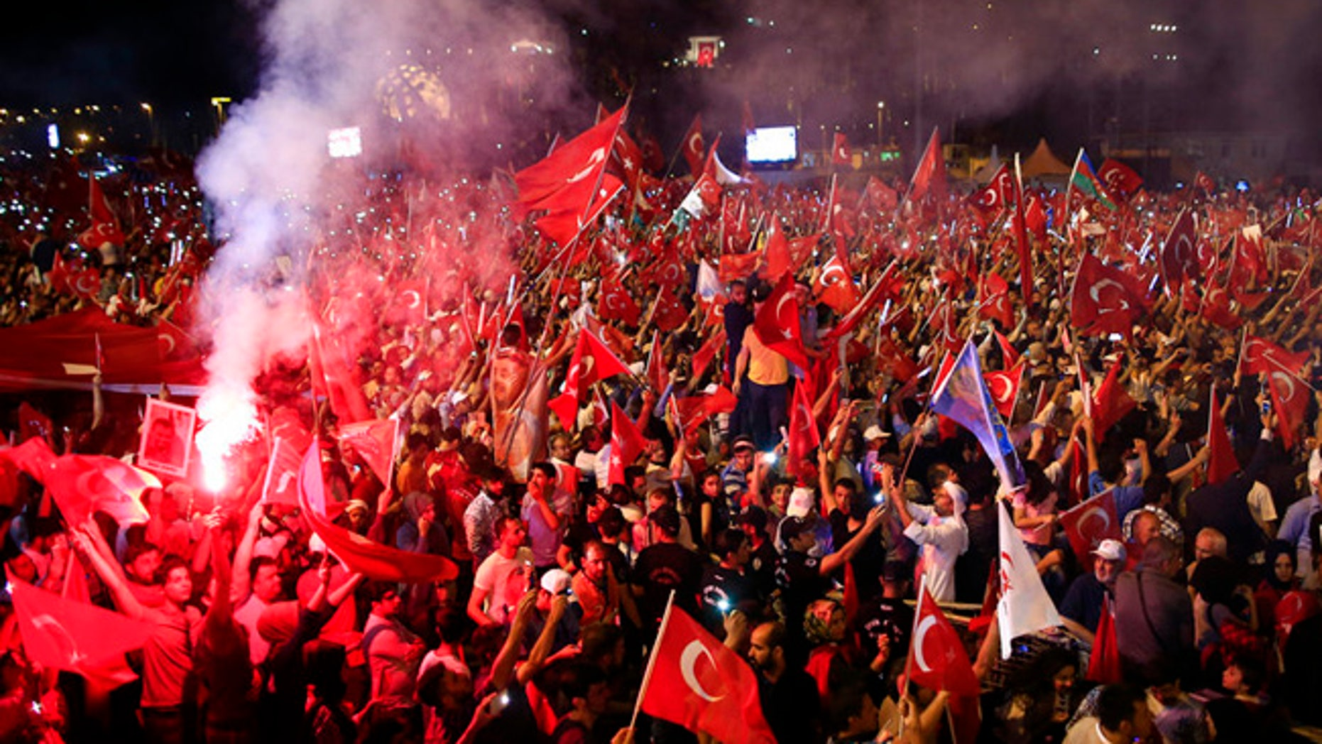"""Crowd cheer as Turkey's President Recep Tayyip Erdogan speaks at the July 15 Martyr's bridge on a """"National Unity March"""" to commemorate the one year anniversary of the July 15, 2016 botched coup attempt, in Istanbul, Saturday, July 15, 2017. Turkey commemorates the first anniversary of the July 15 failed military attempt to overthrow president Erdogan, with a series of events honoring some 250 people, who were killed across Turkey while trying to oppose coup-plotters. (AP Photo/Lefteris Pitarakis)"""