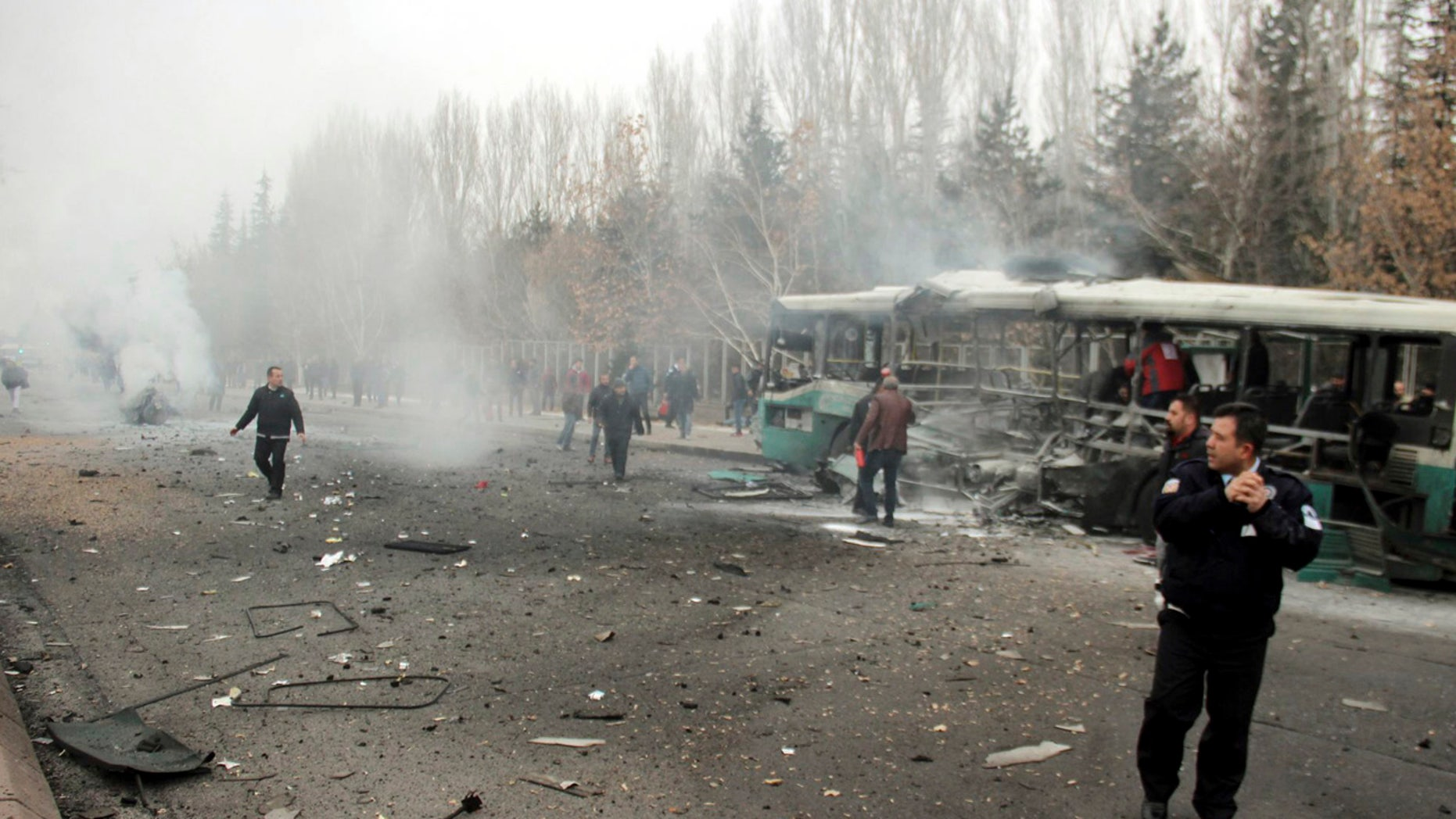Security officials and people at the scene of a car bomb attack in central Anatolian city of Kayseri, Turkey, Saturday, Dec. 17, 2016.
