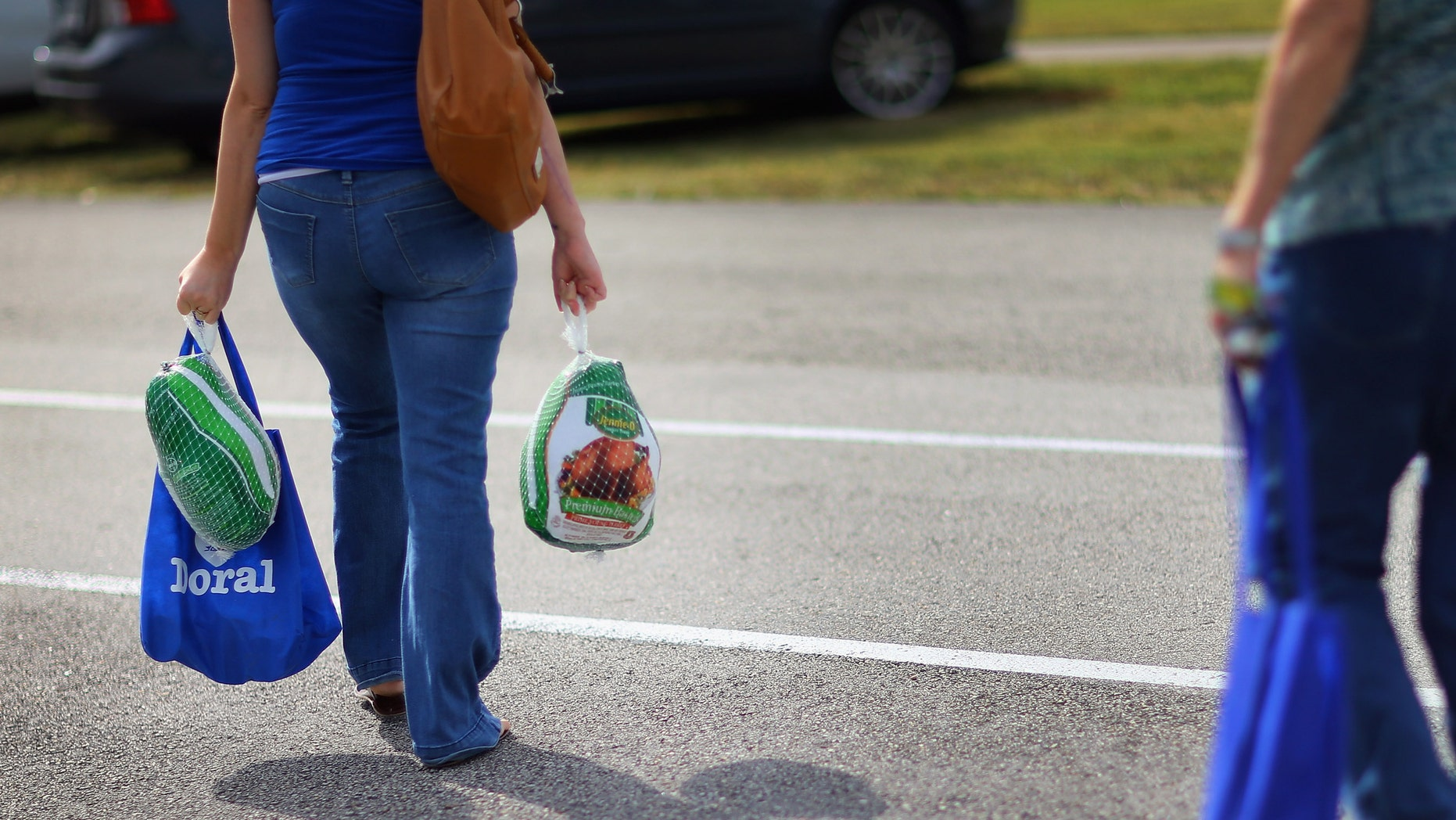 DORAL, FL - NOVEMBER 13:  Jessica Lopez walks away with the turkeys she received at a turkey give-a-way, as people prepare for the upcoming Thanksgiving holiday on November 13, 2012 in Doral, Florida.  The event was put on by the City of Sweetwater and the Miami Dade League of Cities to distribute 1000 turkeys and non-perishable items to four municipalities located throughout Miami-Dade County. (Photo by Joe Raedle/Getty Images)