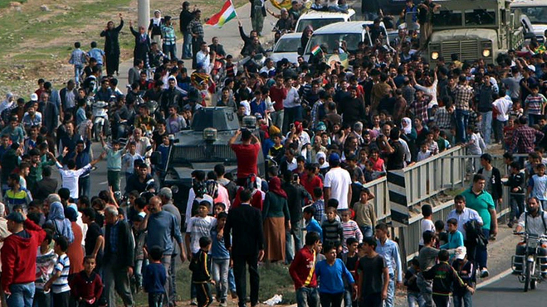 Oct. 29, 2014: Cheering local people surround a group of Iraqi Kurdish Peshmerga troops arrived in Nusaybin, Mardin in southeastern Turkey. The Peshmergas are on their way to Syria to help Syrian Kurds fighting Islamic State extremists in the embattled border town of Kobani.