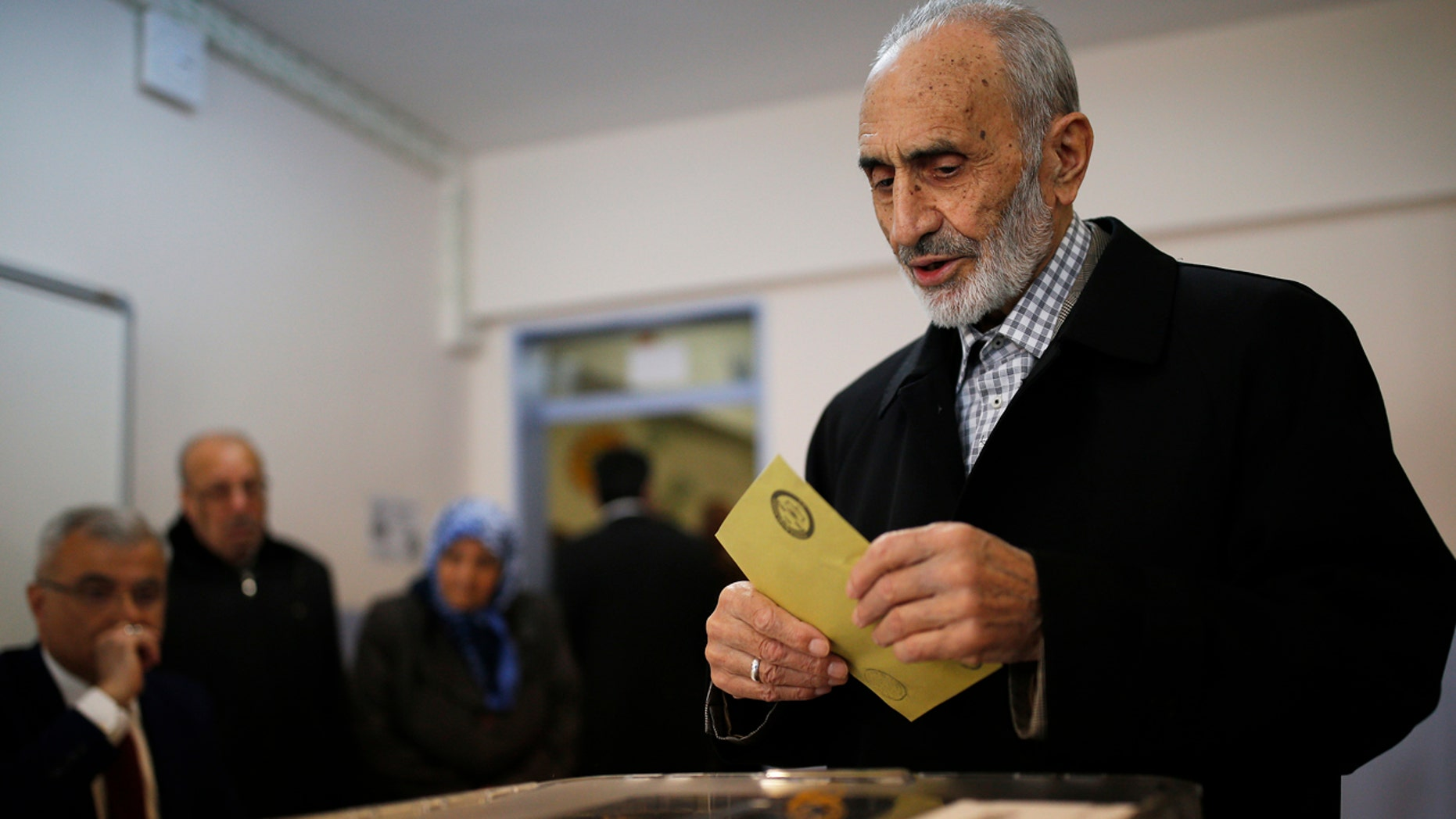 A voter prepares to cast a ballot inside a polling station in Istanbul, Sunday, April 16, 2017.