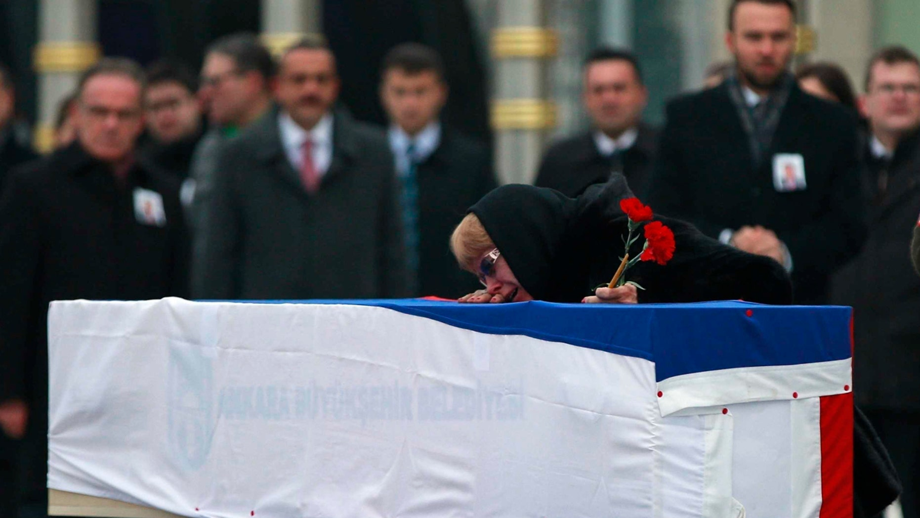 The wife of Russian Ambassador to Turkey Andrei Karlov who was assassinated Monday, cries over her husband's coffin, draped in the Russian flag, during a ceremony at the airport in Ankara, Turkey, Tuesday, Dec, 20, 2016. (AP Photo/ Emrah Gurel)