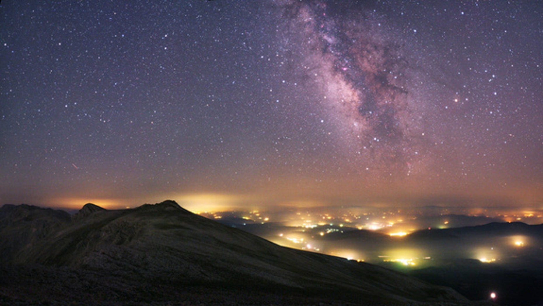A view from the Uludag National Park in Turkey. The Milky Way stretches across the sky above the manmade pockets of hazy lights from the towns and villages below.