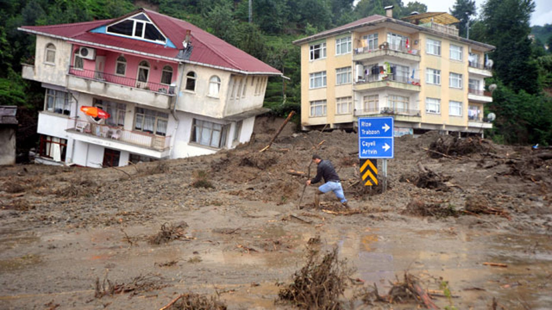 A man walks past a house tilted sideways after landslides and floods triggered by heavy rains swept through a Gundogdu near Turkey's Black Sea coast on Friday, Aug. 27, 2010. People were killed when the landslide collapsed homes in Gundogdu, in the tea-growing Black Sea province of Rize.
