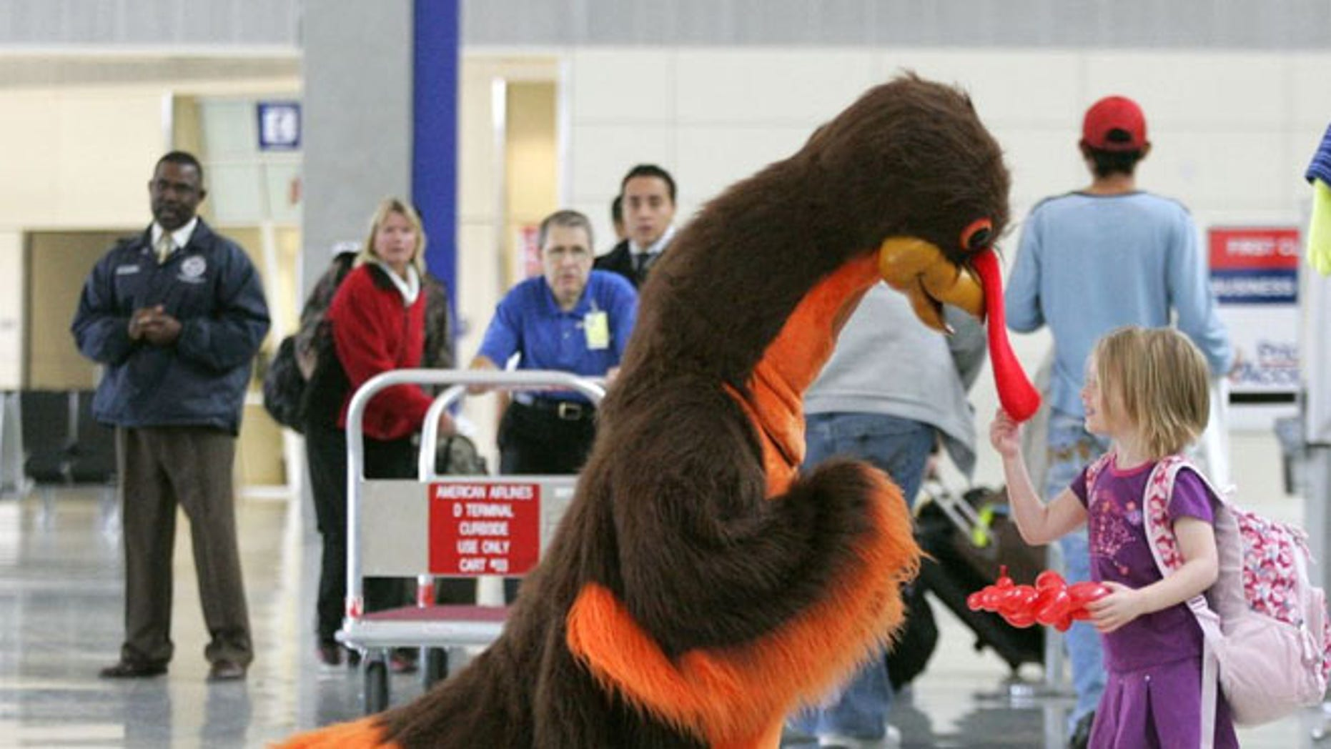 FILE: Abby Harris, 4, checks the wattle on a turkey greeting passengers at Dallas-Fort Worth International Airport in Grapevine, Texas.