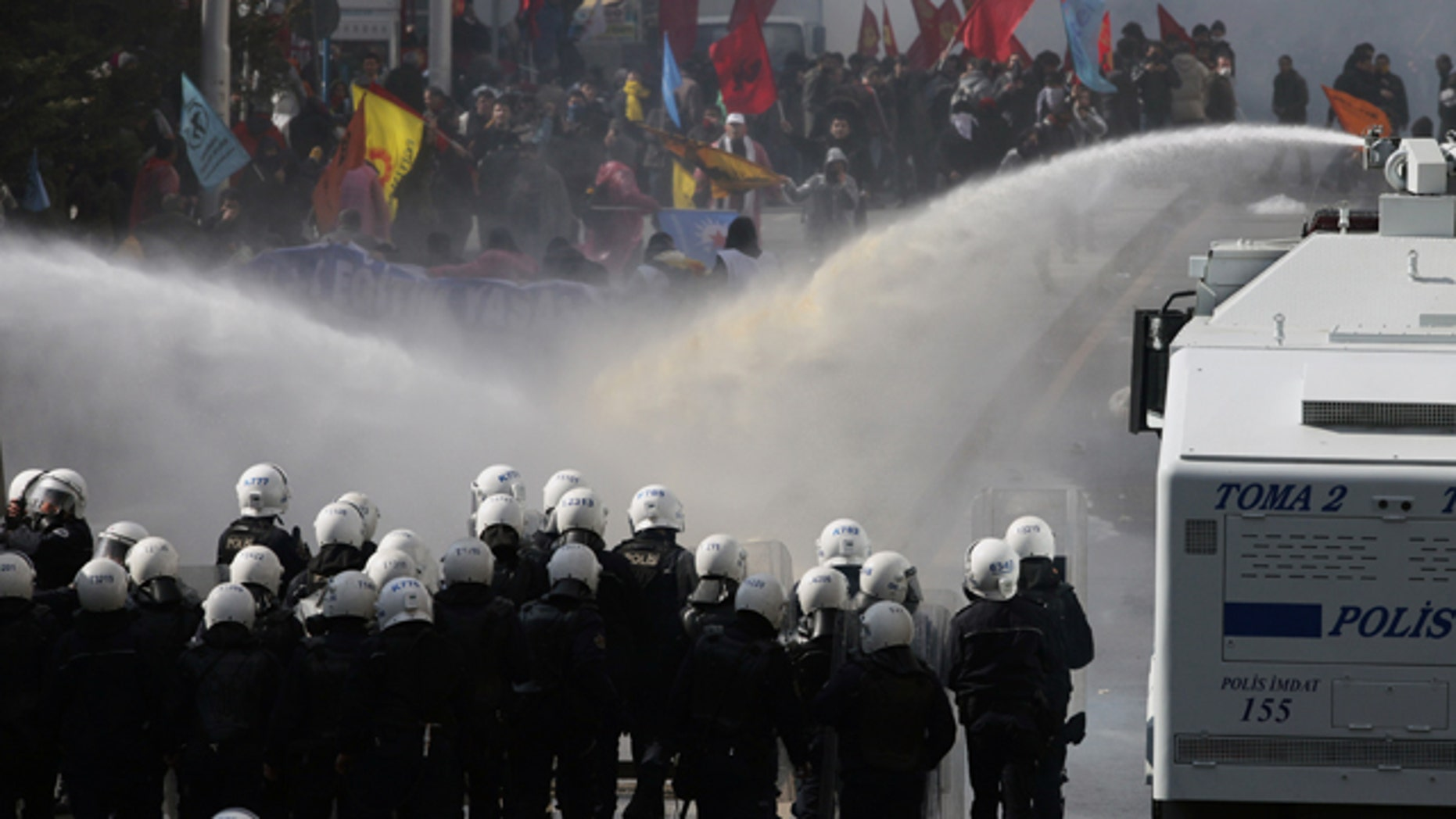 March 29, 2012: People run as Turkish police fire tear gas and water cannons to disperse thousands of people protesting an education reform bill that opponents say will boost the influence of Islamic schools, in Ankara, Turkey.
