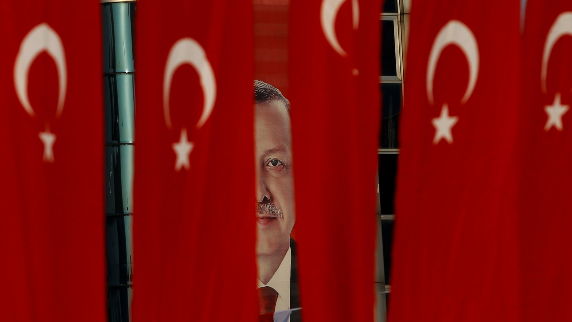 File photo - A picture of Turkish President Tayyip Erdogan is seen through Turkish national flags ahead of the constitutional referendum in Istanbul, Turkey, April 14, 2017. (REUTERS/Alkis Konstantinidis)