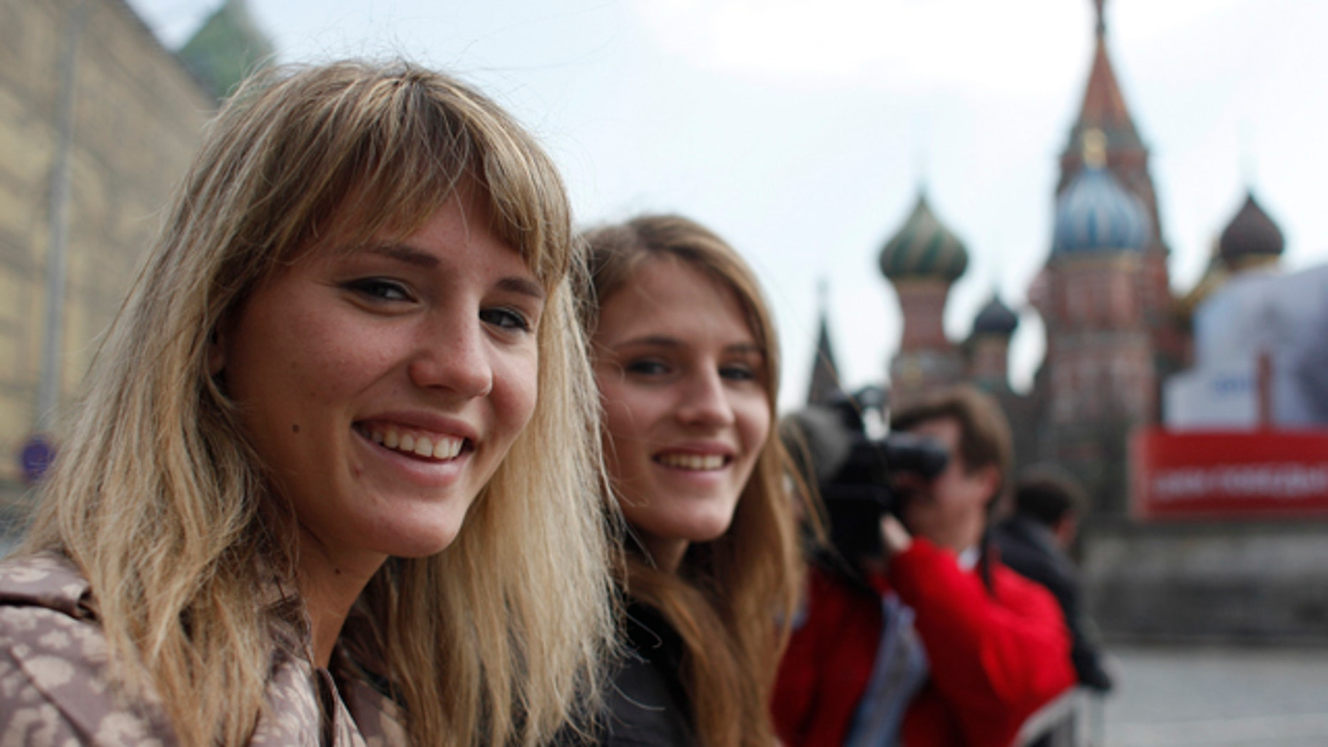 May 3: Twin sisters Jennifer, left, and Jessica, pose for a photo in front of St. Basil's Cathedral in the Red Square in Moscow, Russia. More than 16 years after their American adoptive parents traveled to Russia to collect two malnourished 2-year-old girls named Galina and Svetlana, the twins, now Jessica and Jennifer Allen, have made their first trip back to Children's Home No. 13, reclaiming their Russian heritage, discovering to their delight they feel at home in Russia, too. (AP)