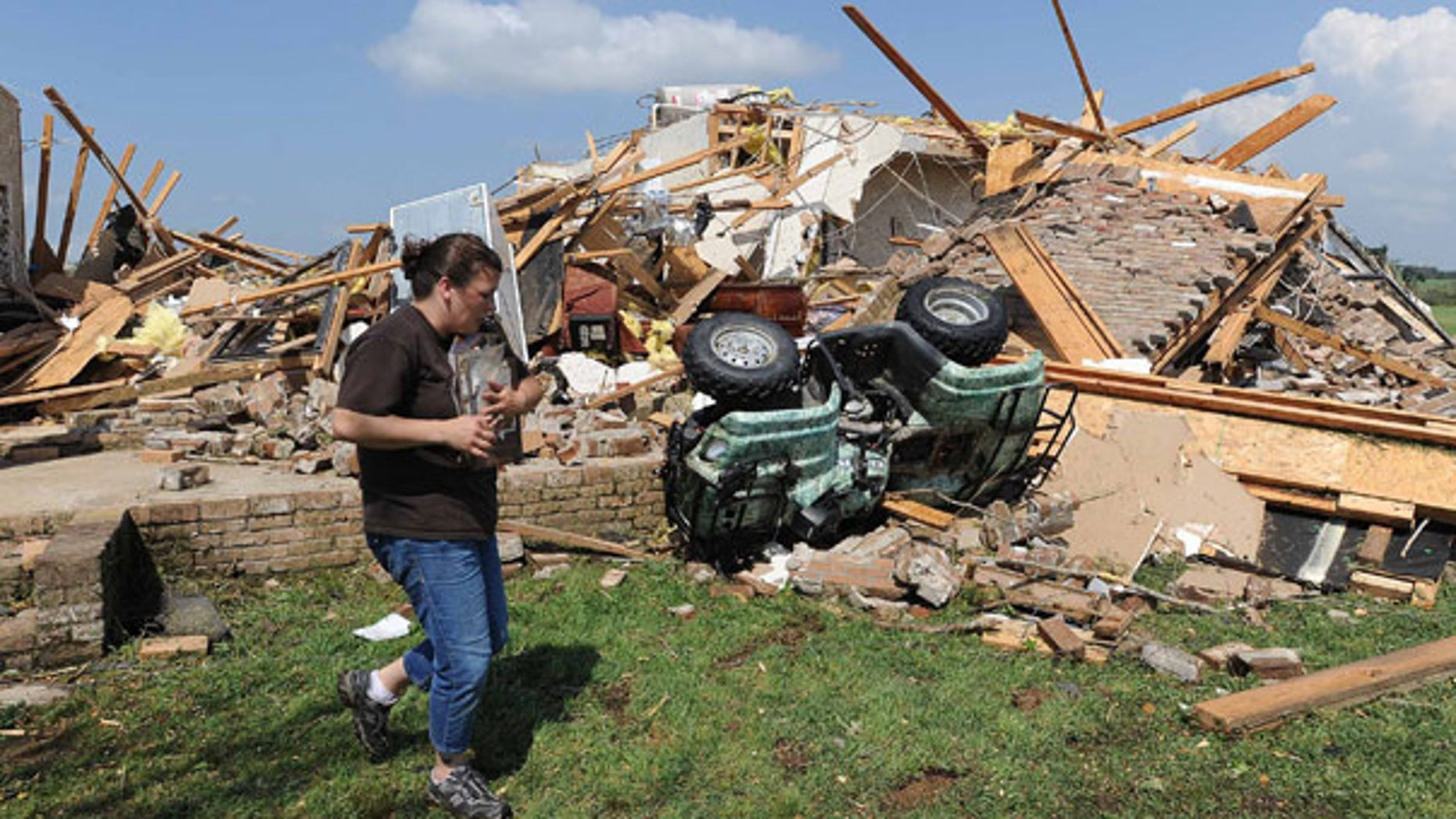 April 24: A woman helps her friend recover photos after a tornado swept through Holmes County, Miss.