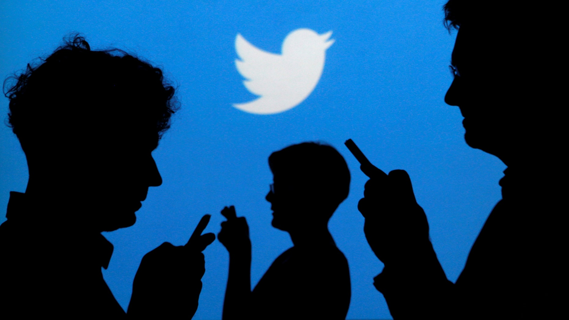 People holding mobile phones are silhouetted against a backdrop projected with the Twitter logo.